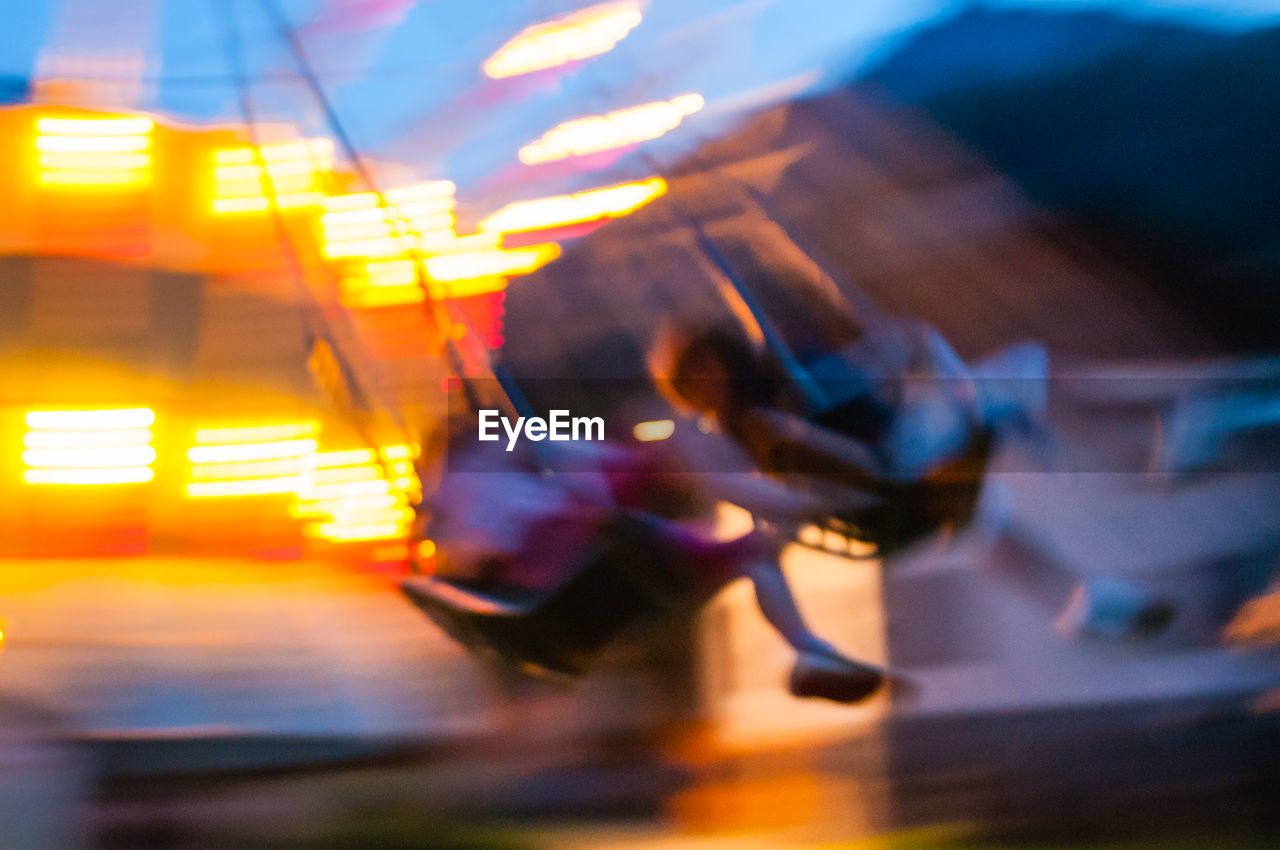 Blurred motion of illuminated chain swing ride at dusk