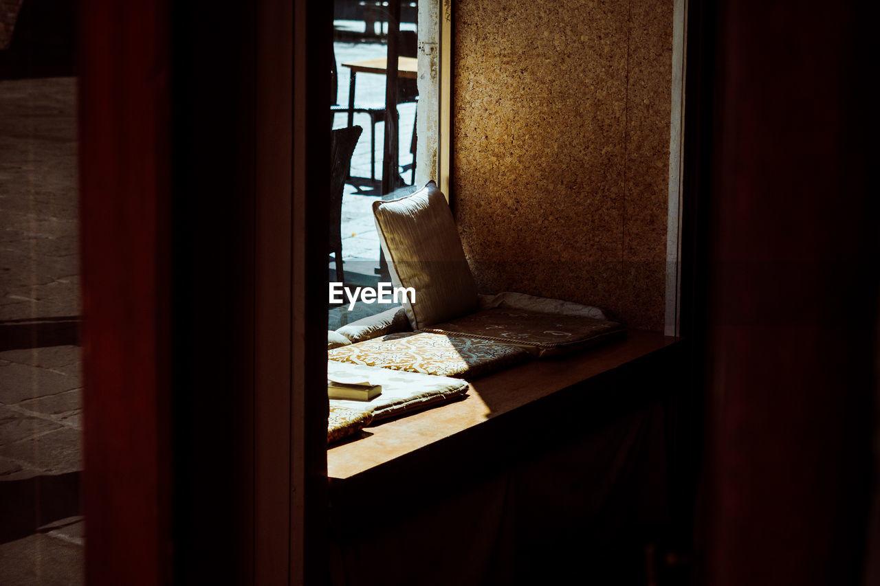 Pillows Arranged On Window In Darkroom