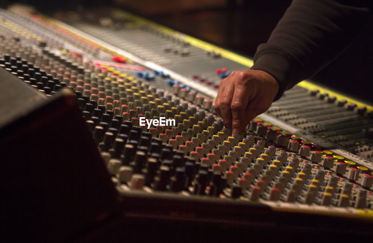 sound mixer, audio equipment, human hand, sound recording equipment, technology, indoors, studio, music, recording studio, human body part, control, hand, control panel, selective focus, one person, adjusting, equipment, arts culture and entertainment, mixing, rock music, finger, complexity, push button