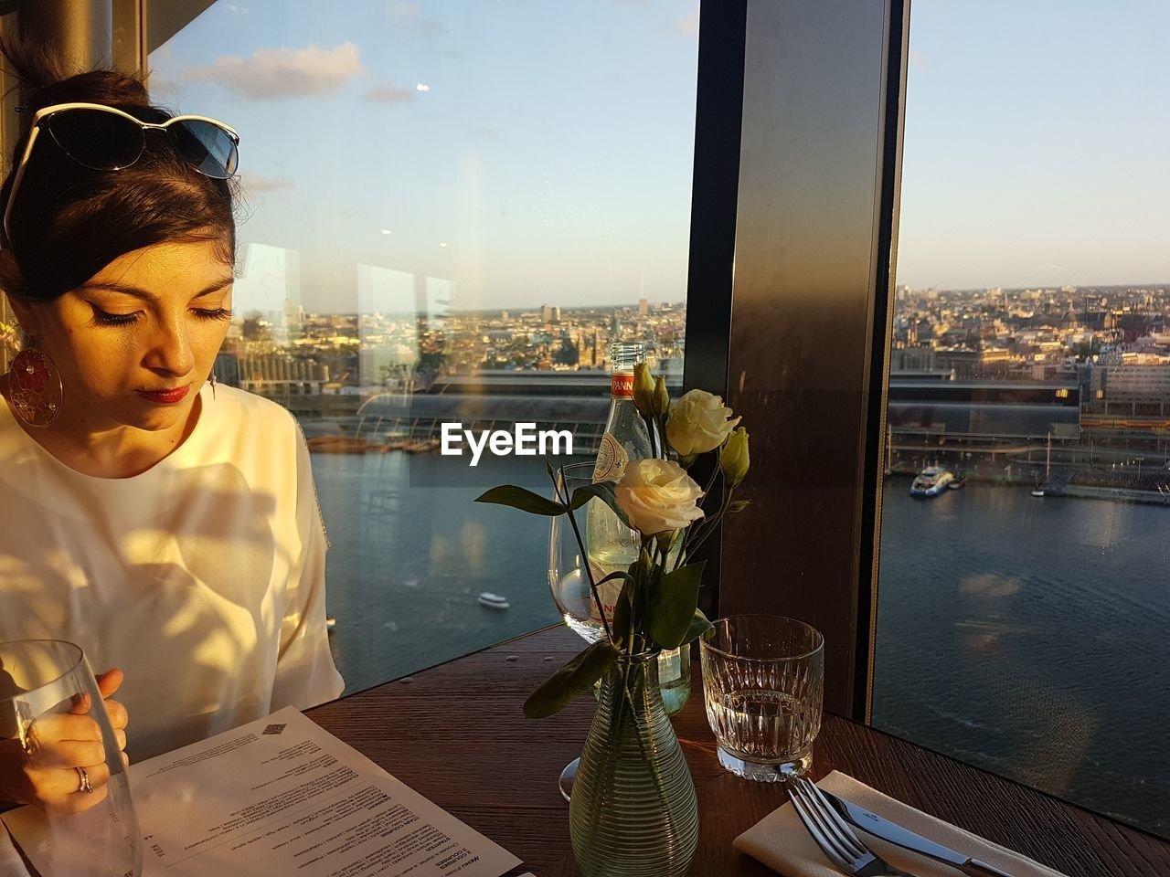 Woman reading menu while sitting by window at restaurant