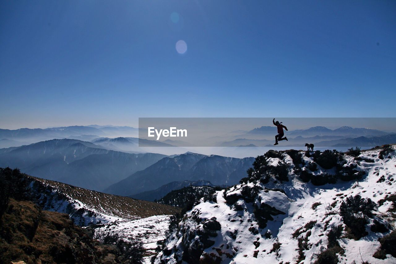 Silhouette man jumping on mountain against clear blue sky during sunny day