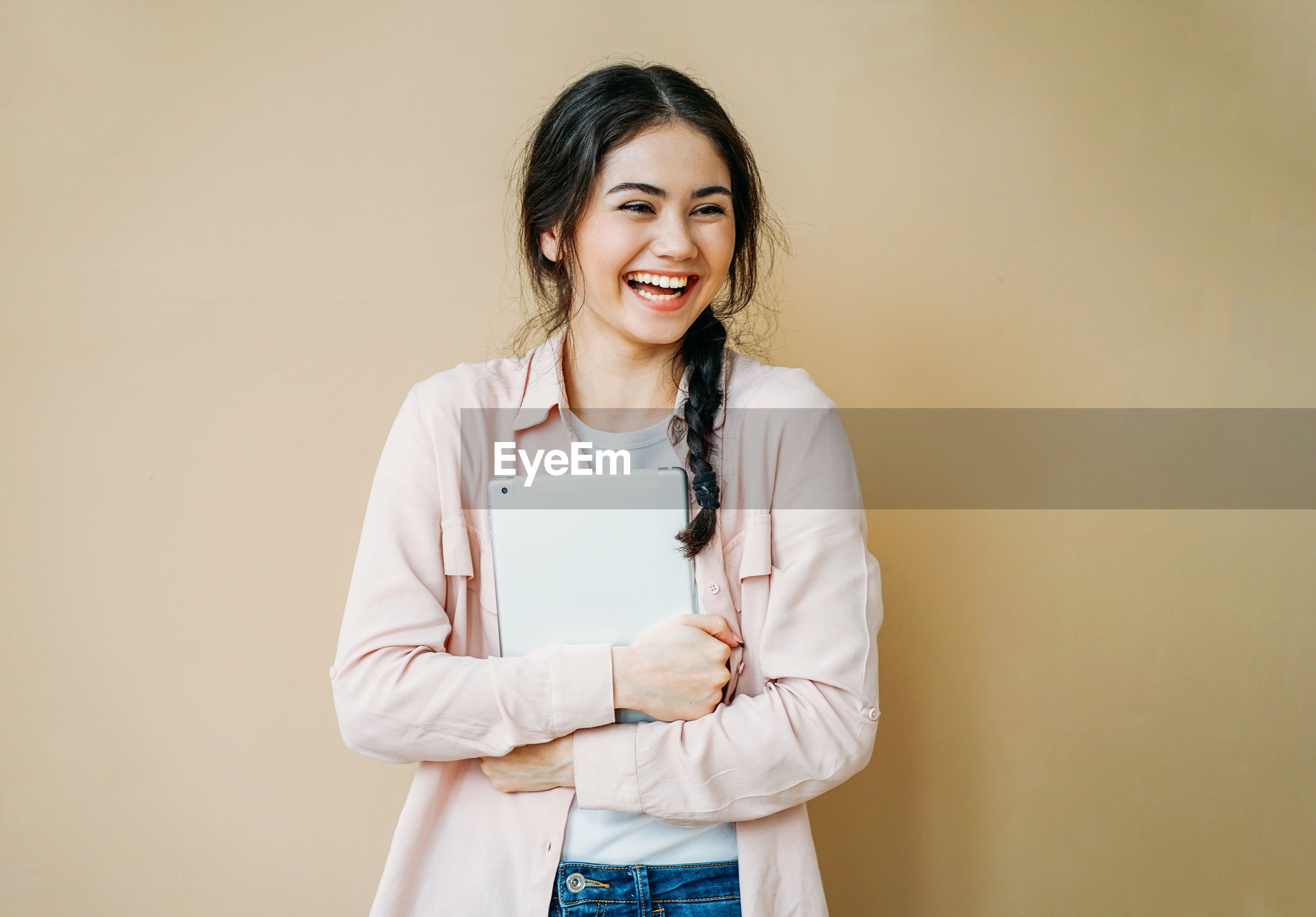 Smiling young woman looking away standing against beige background