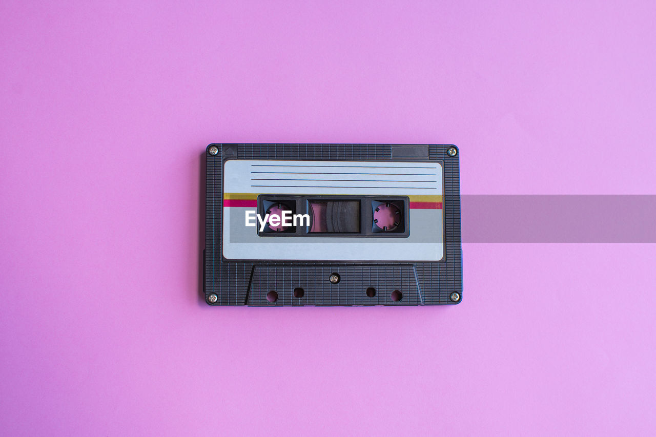 pink color, technology, pink background, indoors, colored background, connection, close-up, copy space, wall - building feature, communication, no people, studio shot, wireless technology, purple, directly above, still life, screen, telephone