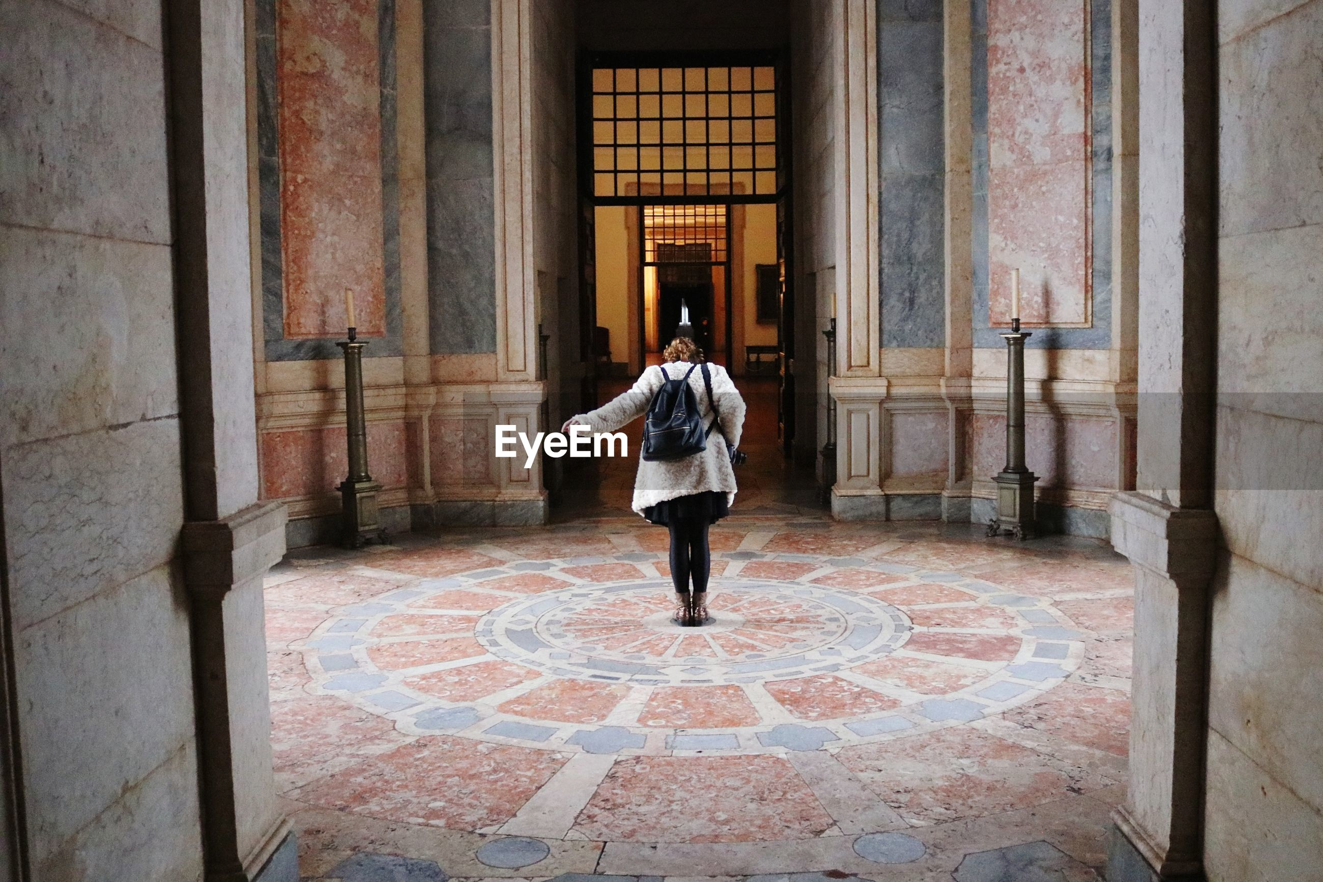 Rear view of woman standing in historic building