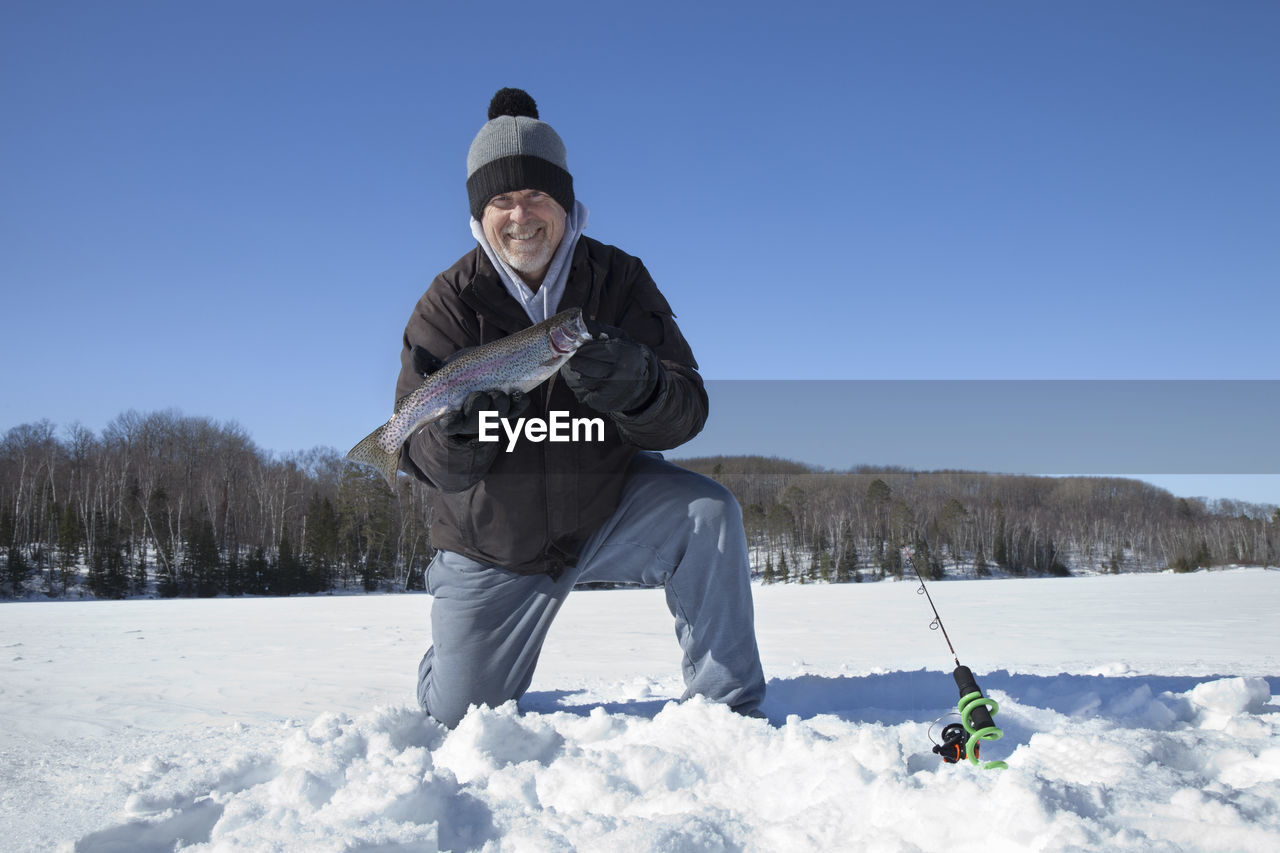 Portrait of smiling man holding fish on snow field against clear blue sky
