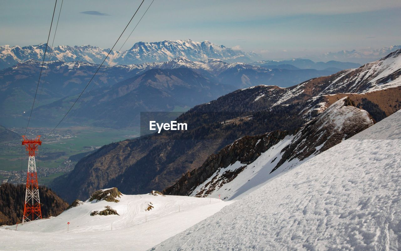 mountain, snow, cold temperature, winter, scenics - nature, beauty in nature, mountain range, landscape, environment, sky, nature, snowcapped mountain, cable car, cable, non-urban scene, tranquil scene, day, transportation, tranquility, no people, outdoors, mountain peak, range, formation