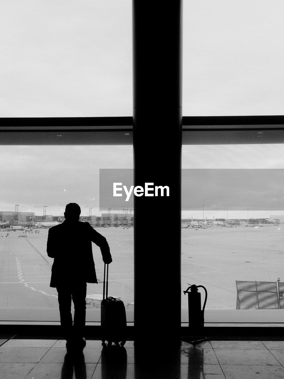 Silhouette man with luggage standing in airport