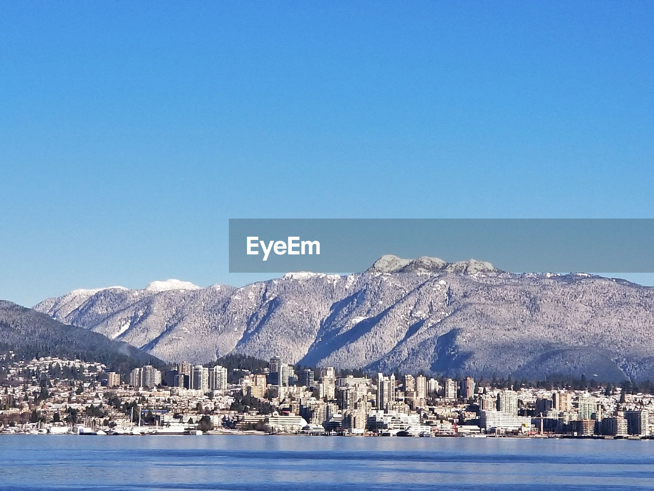 SCENIC VIEW OF SEA AND SNOWCAPPED MOUNTAIN AGAINST CLEAR BLUE SKY