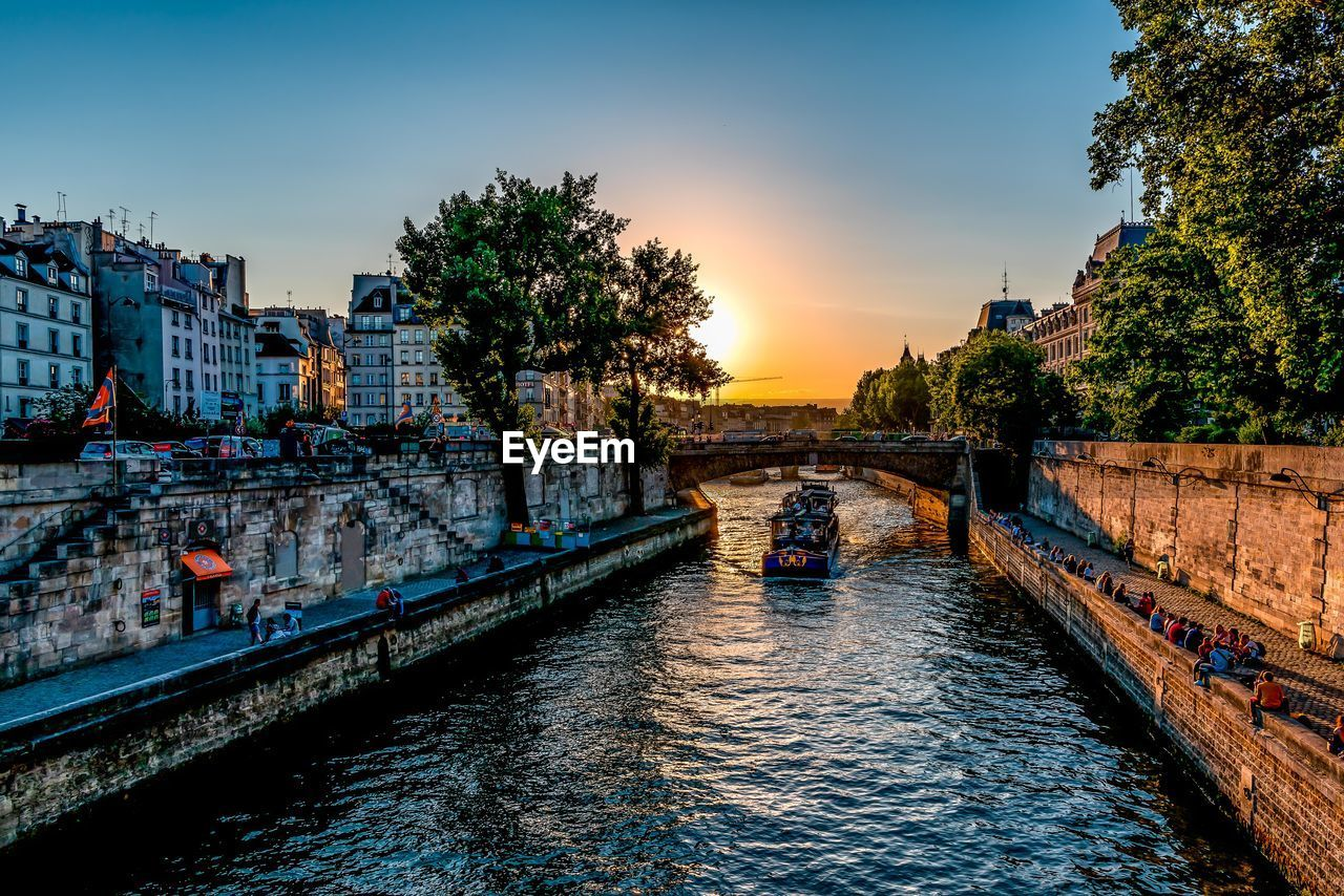 Canal in city during sunset