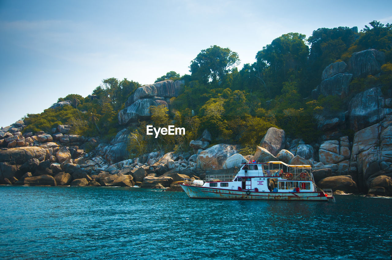 water, sky, waterfront, beauty in nature, nature, nautical vessel, mode of transportation, transportation, rock, day, tree, plant, rock - object, real people, solid, scenics - nature, sea, tranquility, rock formation, outdoors