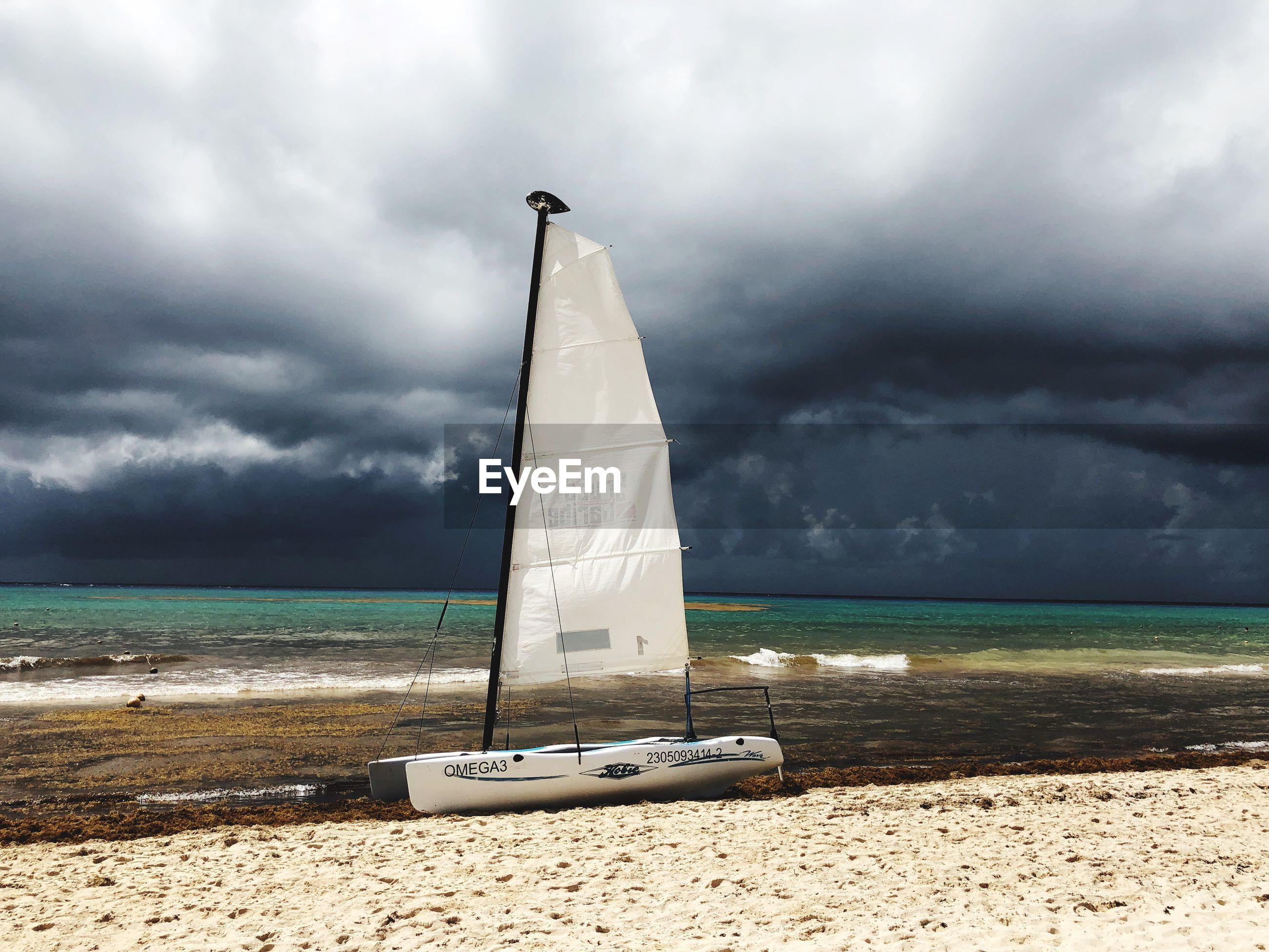SAILBOAT ON BEACH BY SEA AGAINST SKY