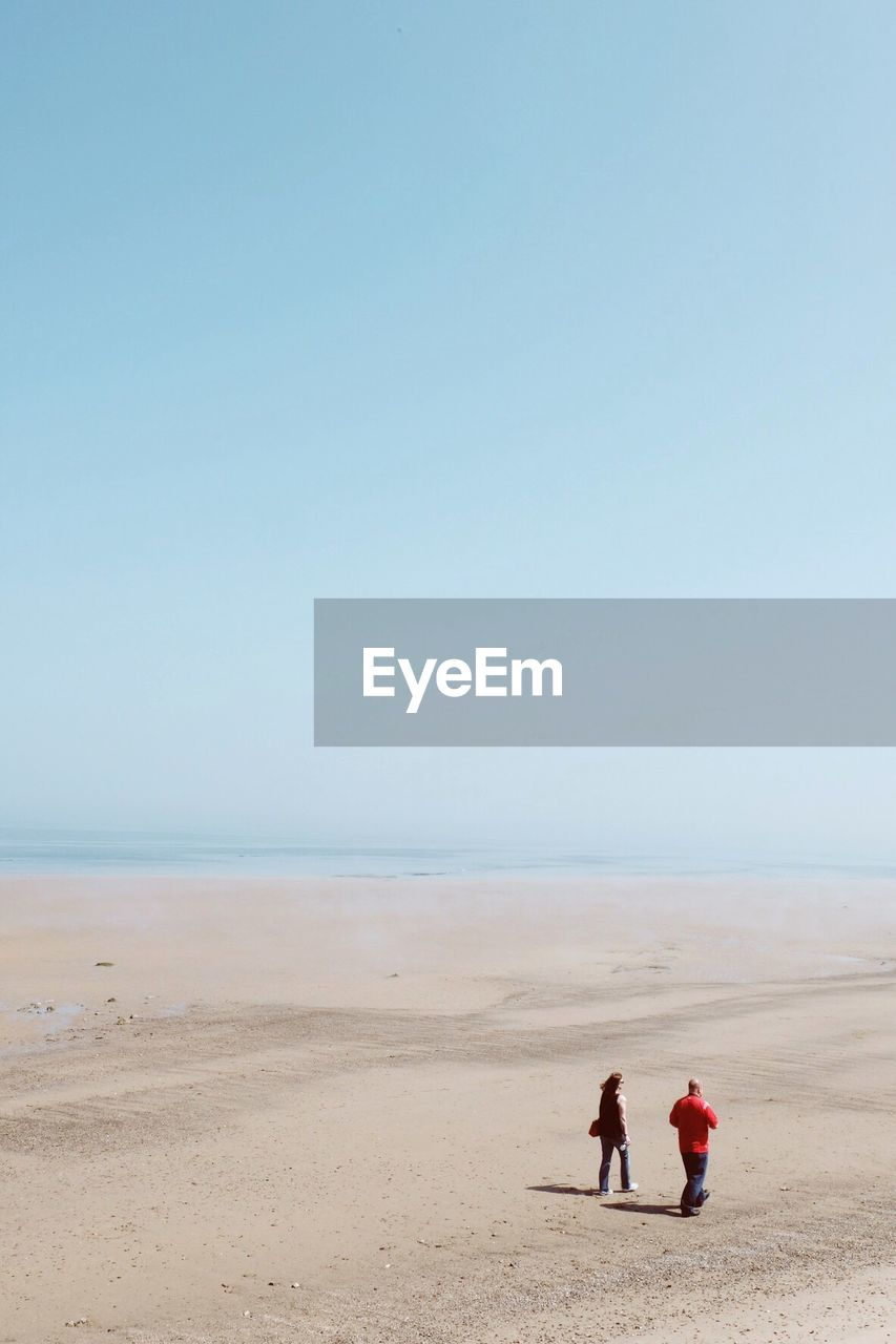 High Angle View Of Couple Walking At Beach Against Sky