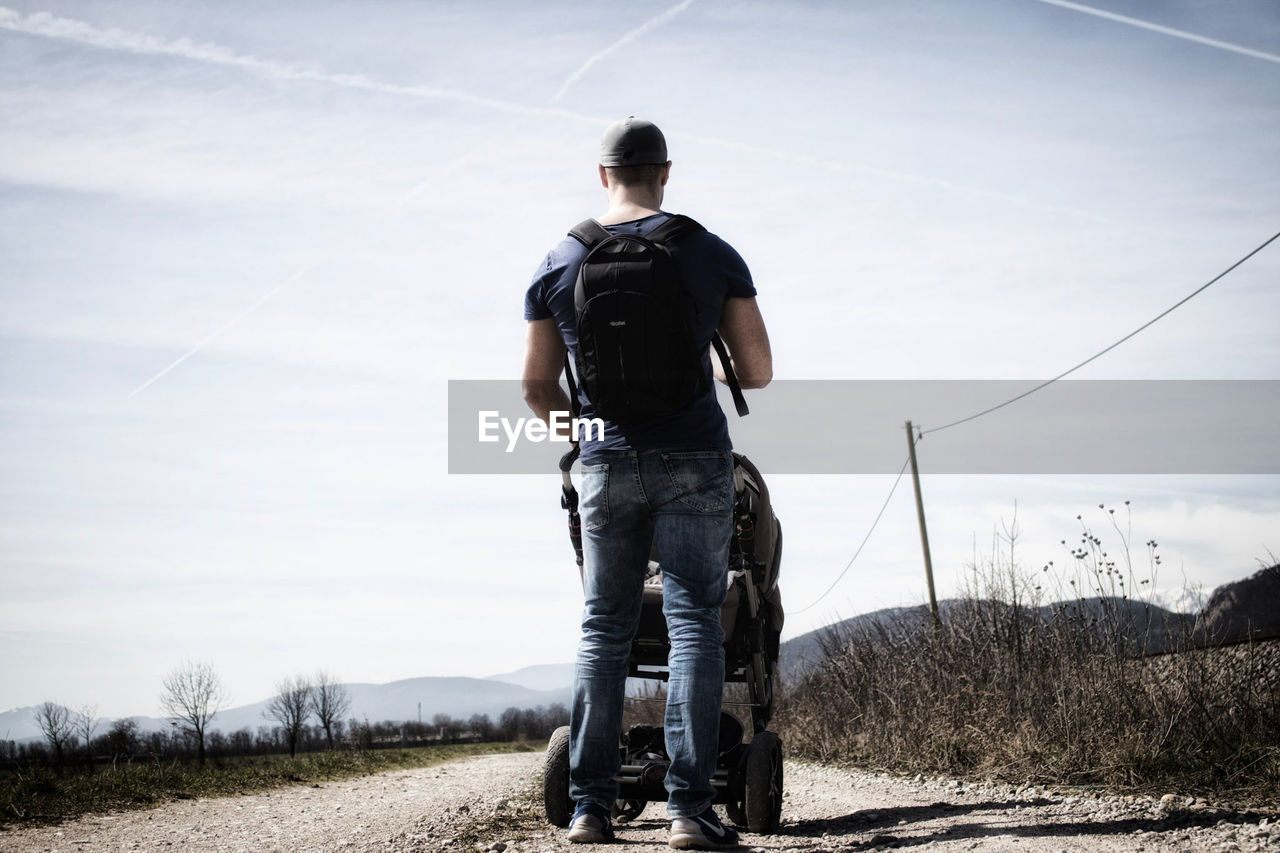 Rear View Of Man With Baby Carriage Standing On Field Against Sky During Sunny Day