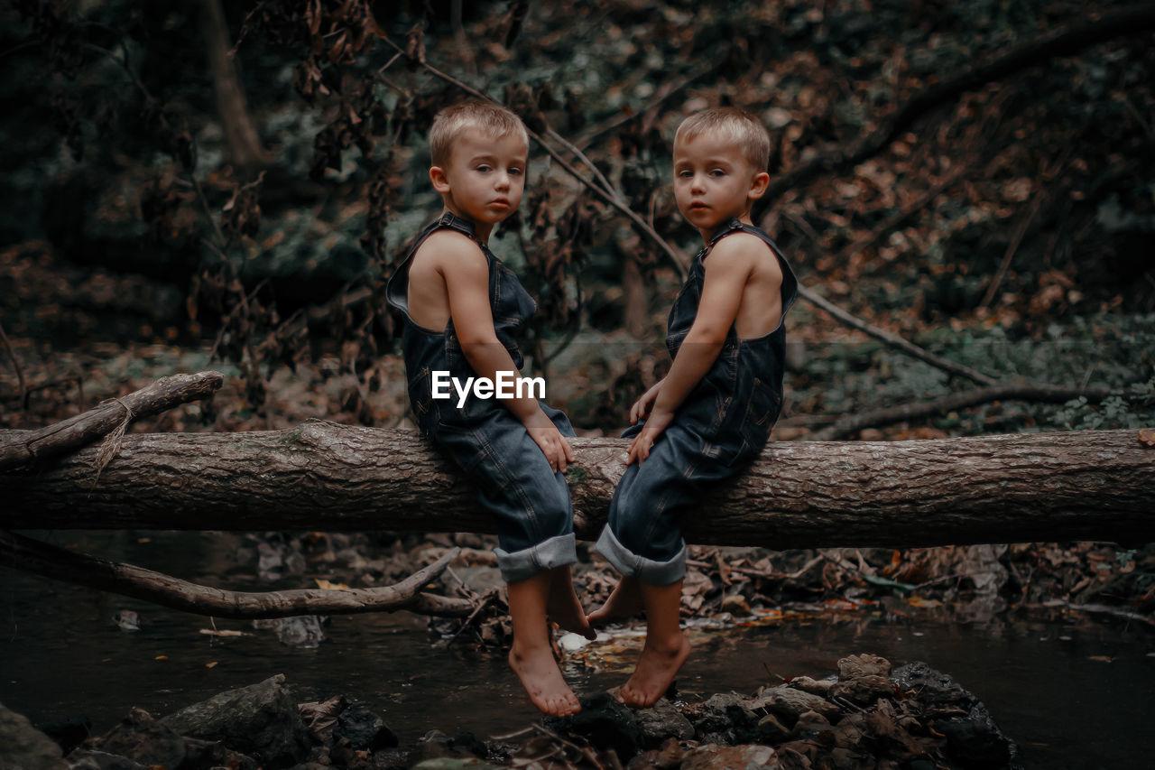 Full length of twin siblings sitting on wood
