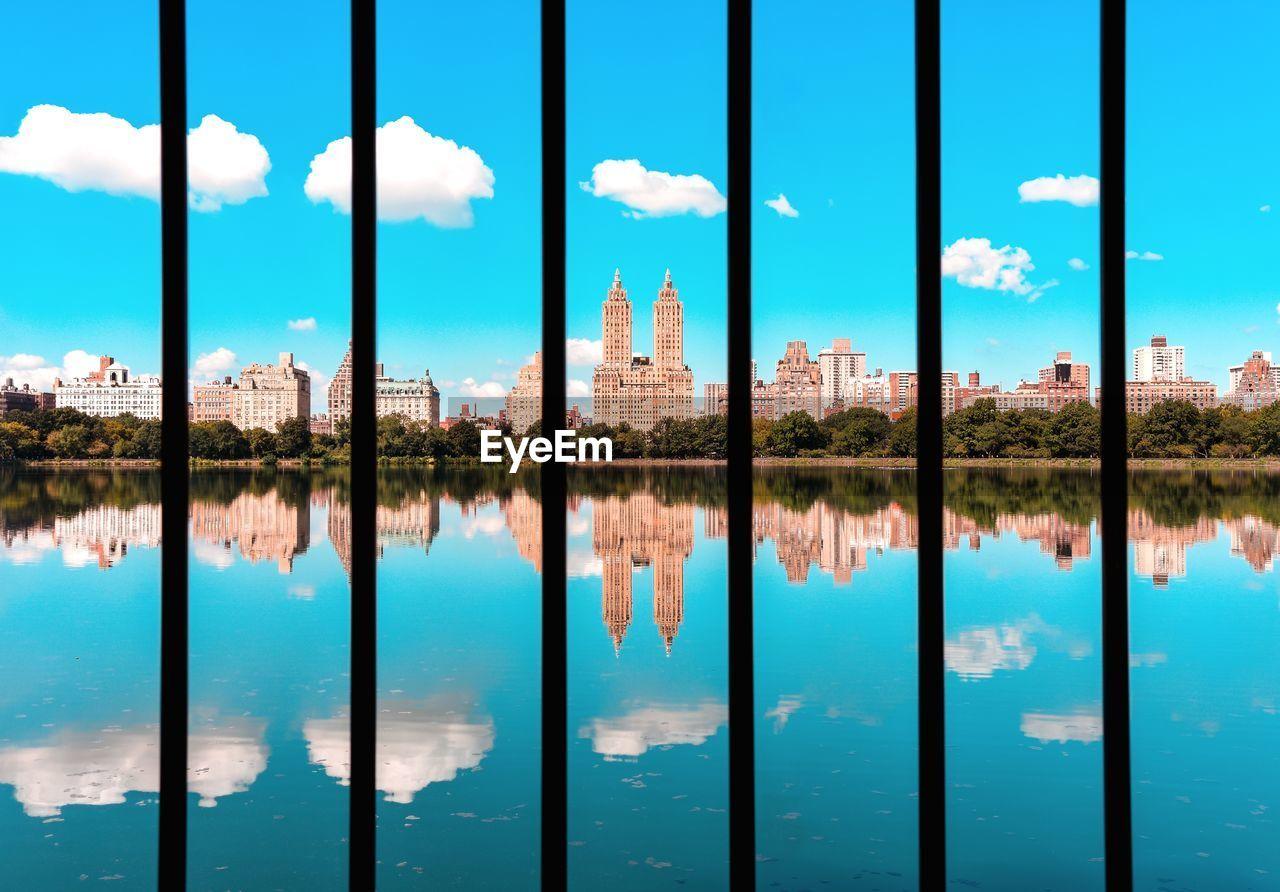 Reflection Of Buildings In Reservoir Against Blue Sky