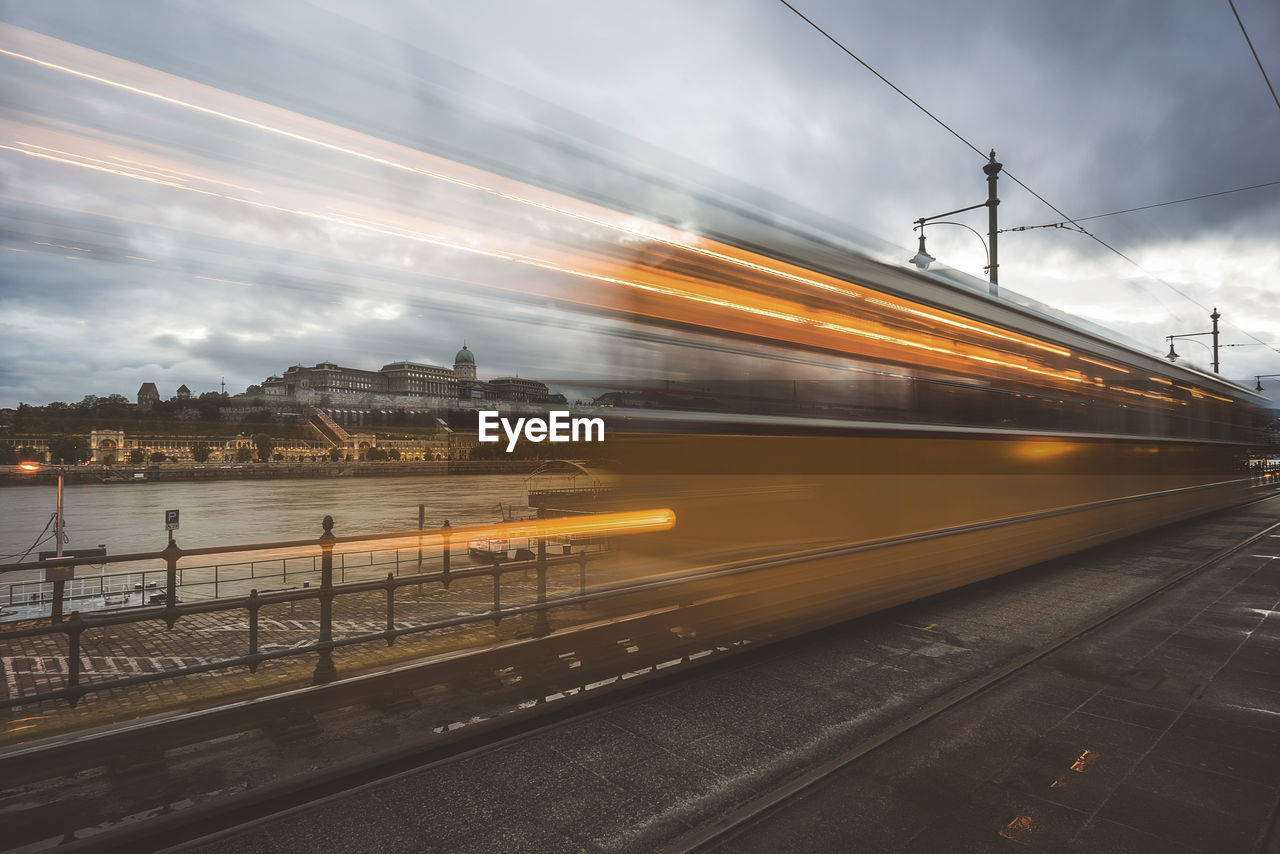 rail transportation, public transportation, transportation, sky, motion, cloud - sky, railroad track, train, architecture, blurred motion, speed, mode of transportation, track, nature, on the move, train - vehicle, long exposure, built structure, no people, travel, outdoors