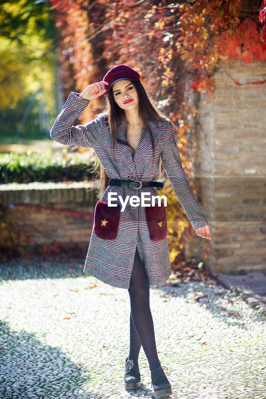 Portrait of beautiful model standing against autumn plants