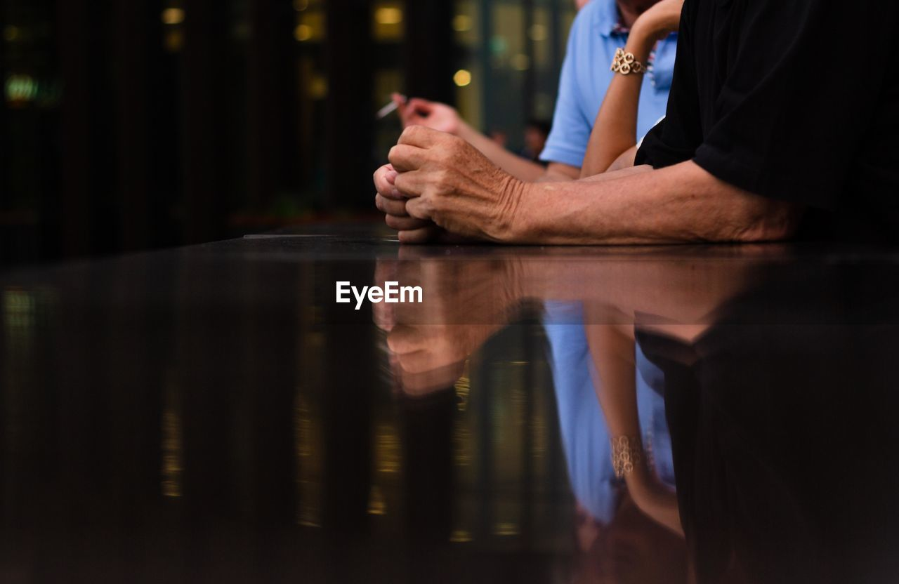 Midsection of people reflecting on glass table