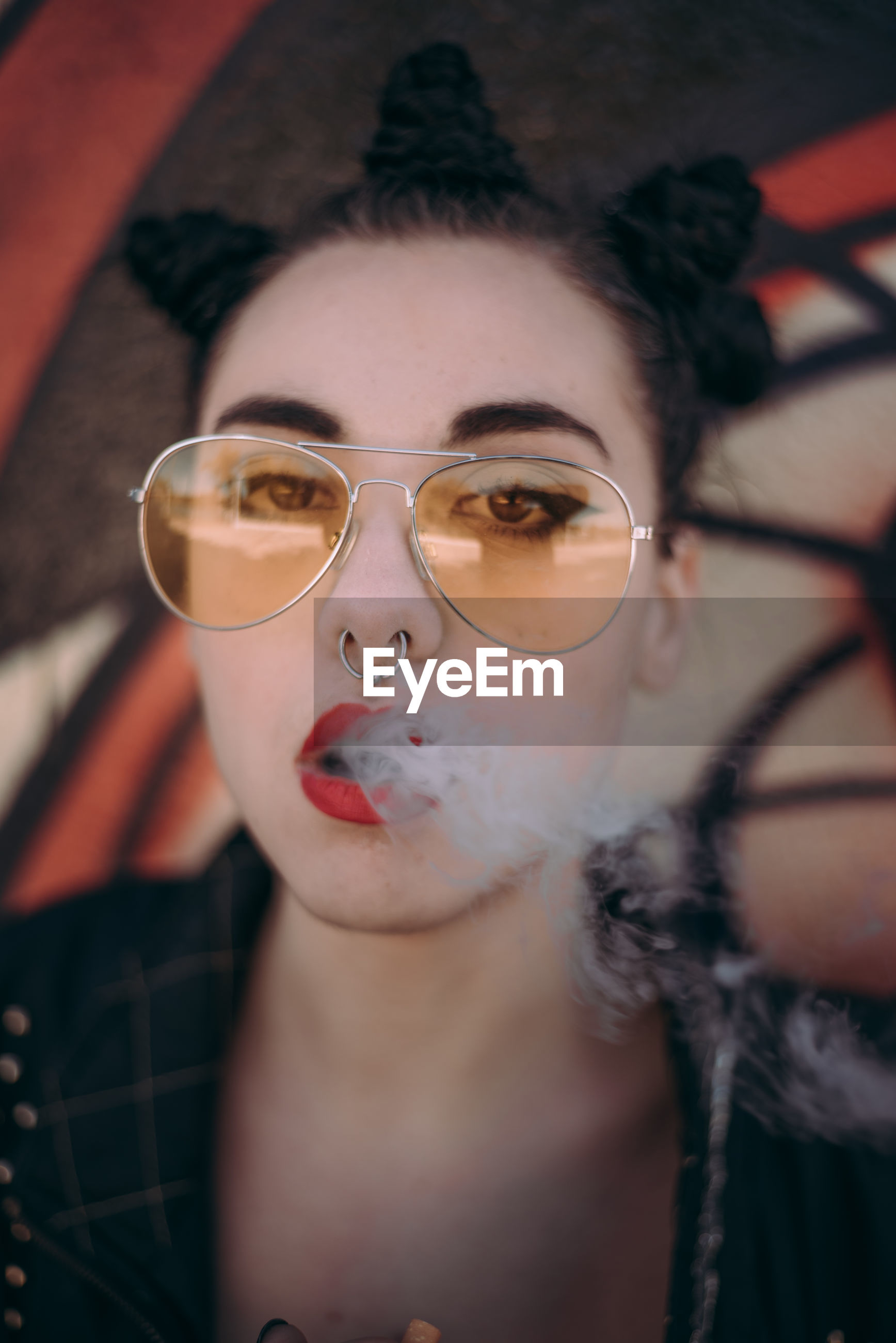 Close-up portrait of young woman smoking cigarette by graffiti wall