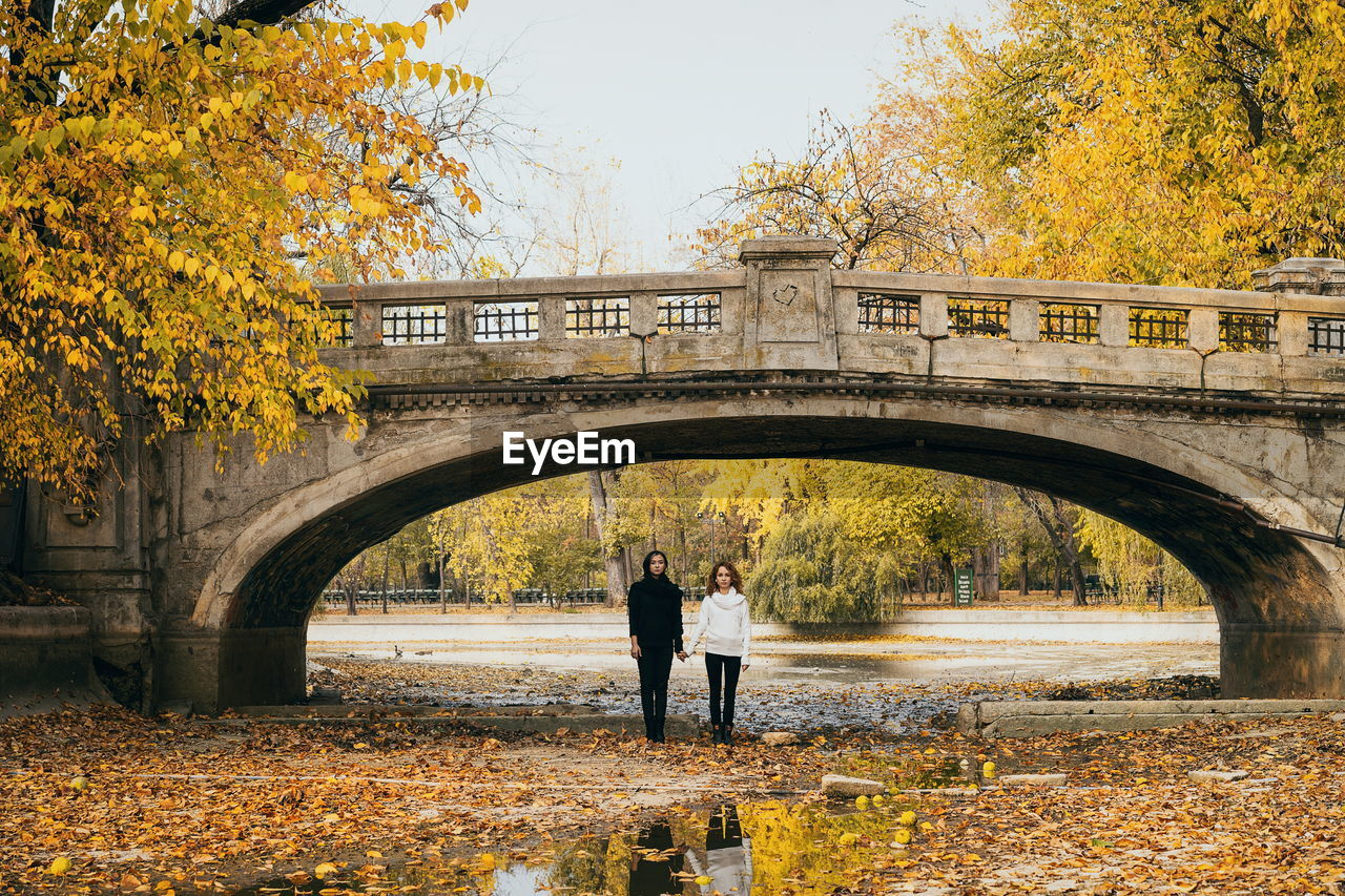 Lesbian Couple Holding Hands While Standing At Arch Bridge During Autumn