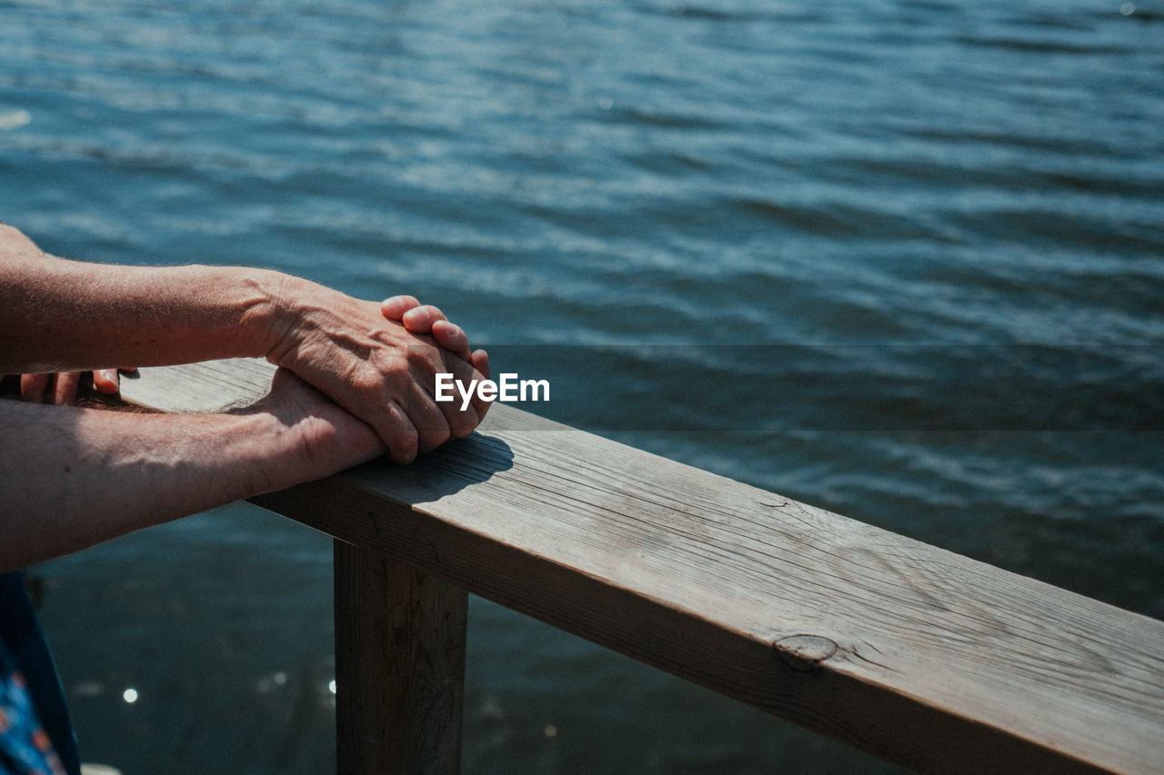 Cropped image of couple holding hands on railing against sea