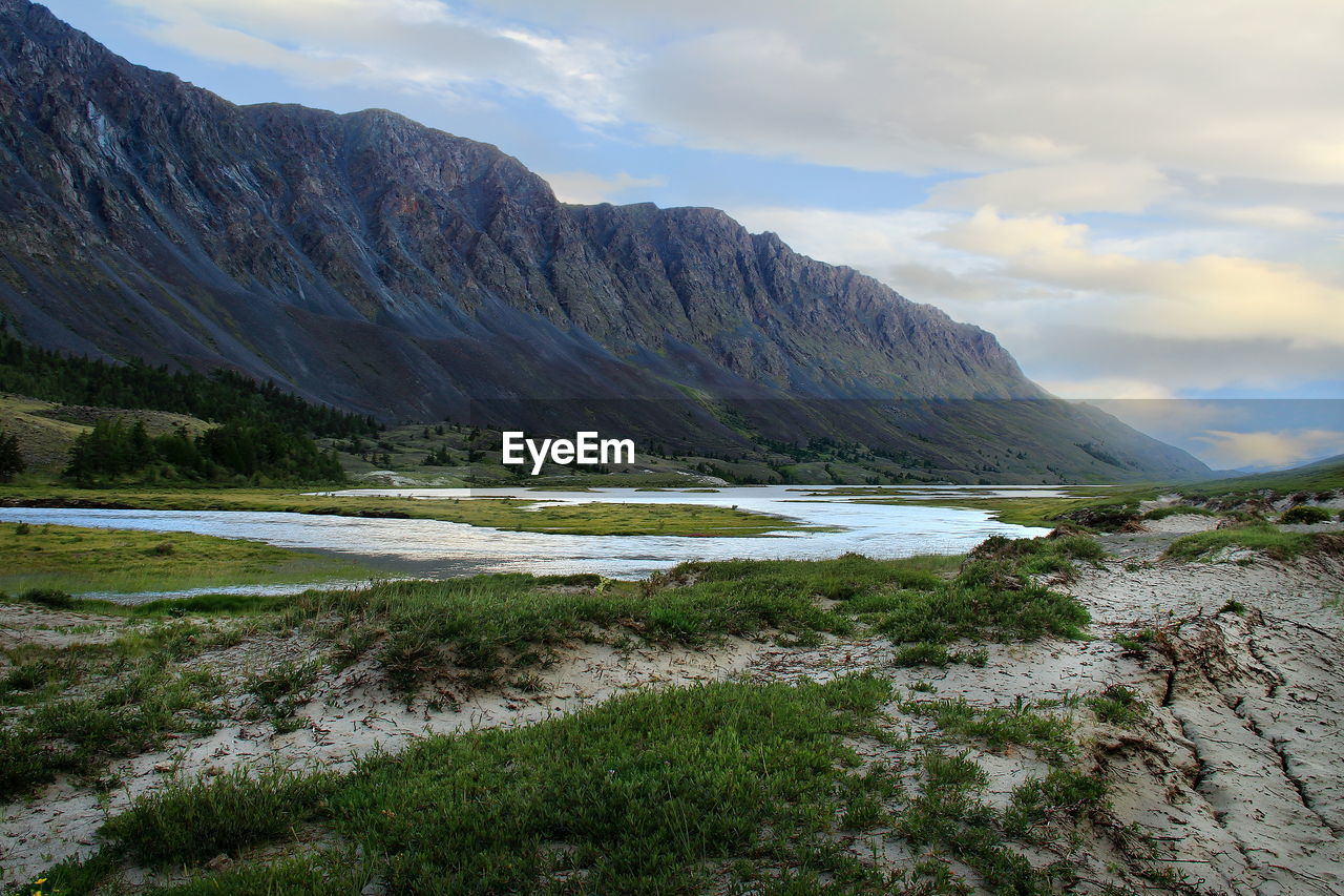 Alpine valley with river, grass, trees and a huge mountain range at sunset