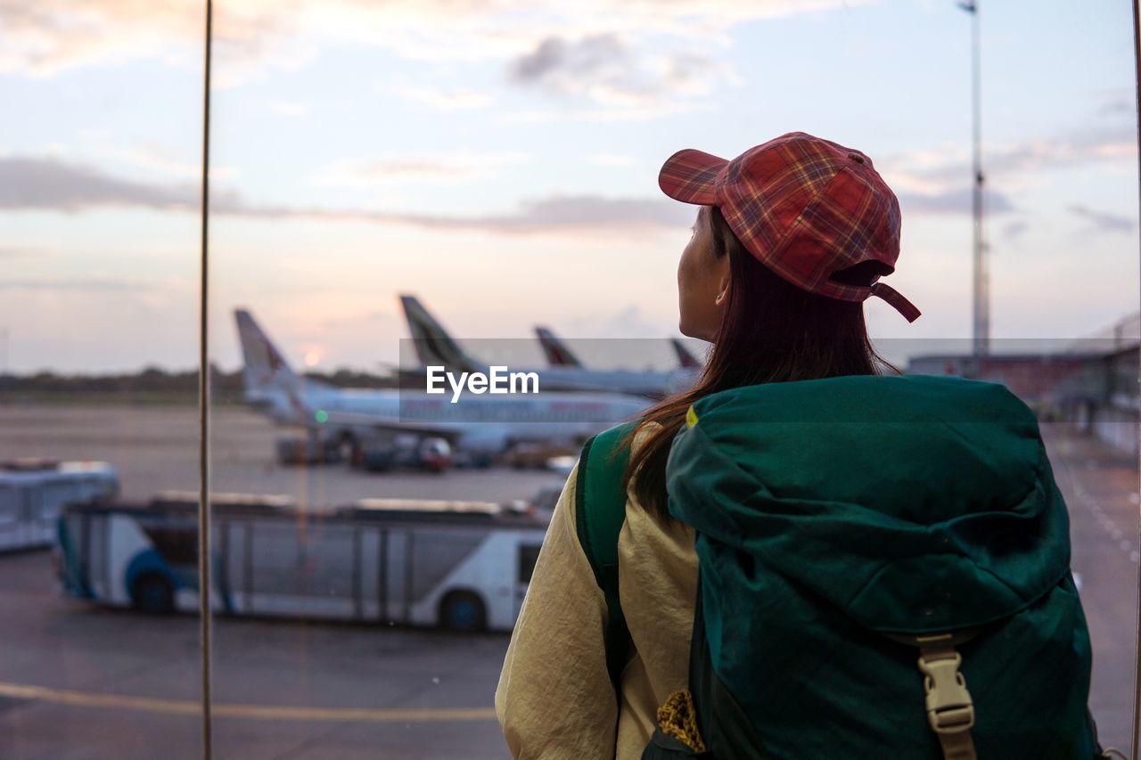 REAR VIEW OF MAN AT AIRPORT
