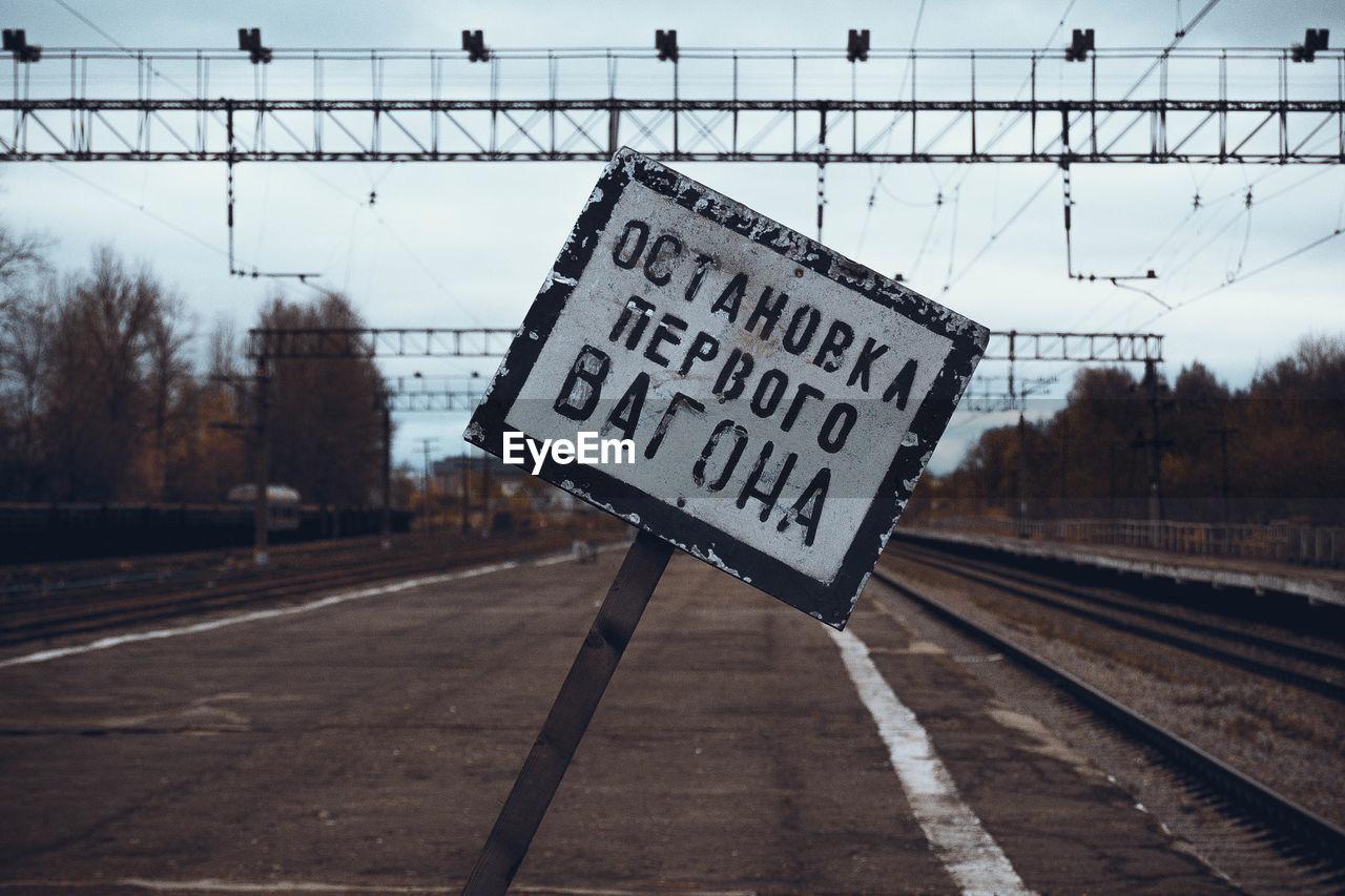 Signboard on railroad station platform against sky