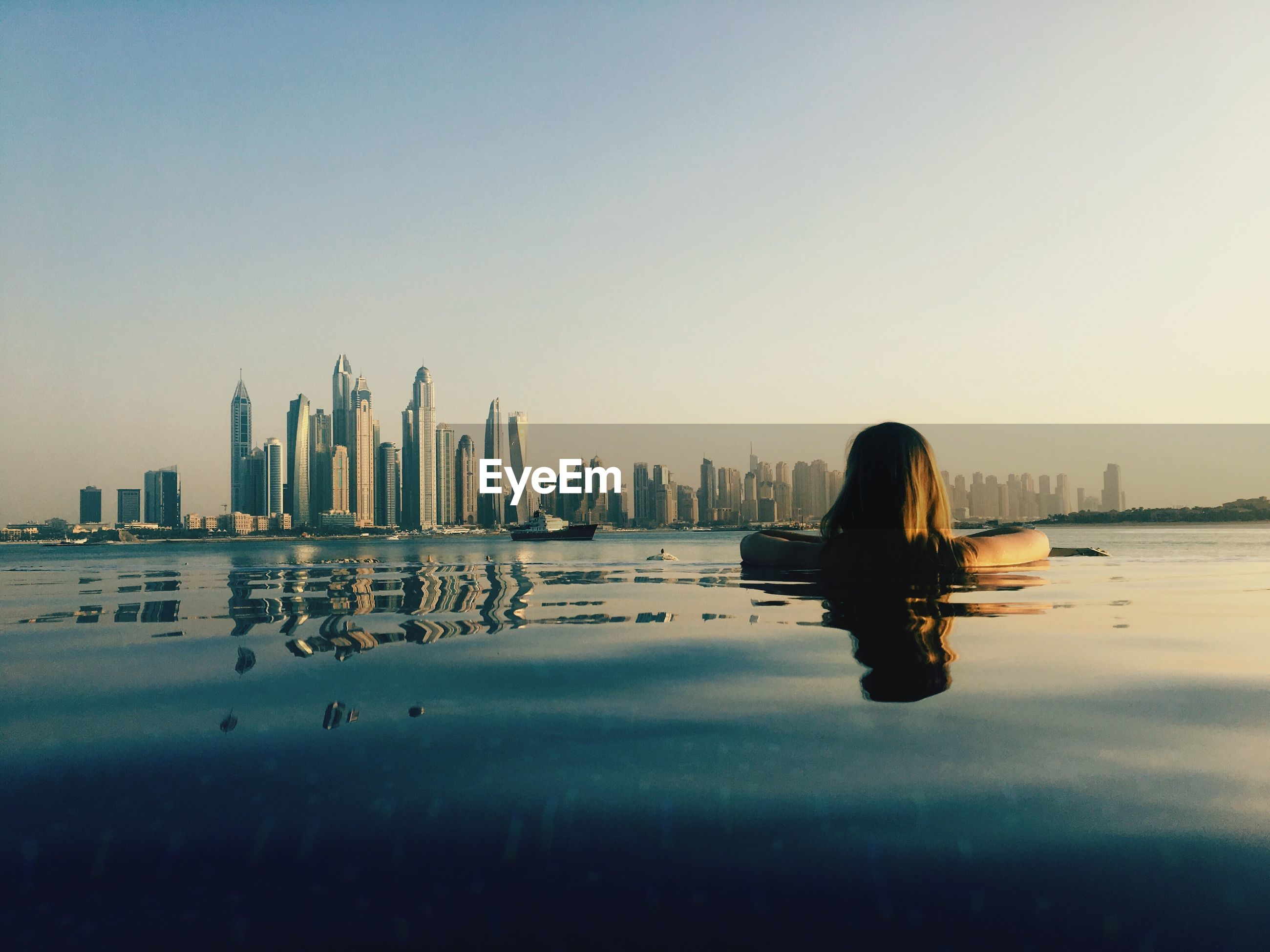 Rear view of woman looking at modern building while swimming in infinity pool against clear sky during sunset