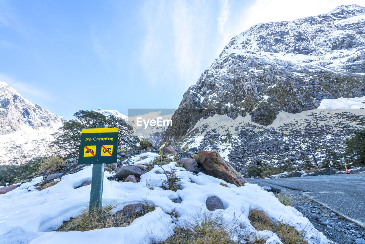 cold temperature, winter, snow, sign, mountain, nature, beauty in nature, sky, communication, scenics - nature, day, tranquility, text, no people, information, non-urban scene, cloud - sky, environment, road, guidance, outdoors, snowcapped mountain, formation