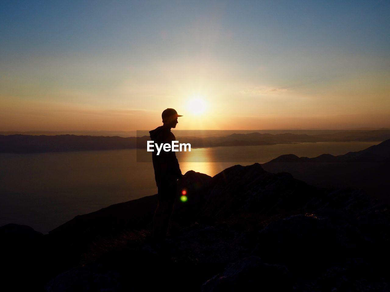 sunset, sky, silhouette, beauty in nature, scenics - nature, standing, solid, tranquility, one person, rock, real people, rock - object, tranquil scene, leisure activity, lifestyles, orange color, nature, non-urban scene, mountain, idyllic, sun, outdoors, looking at view