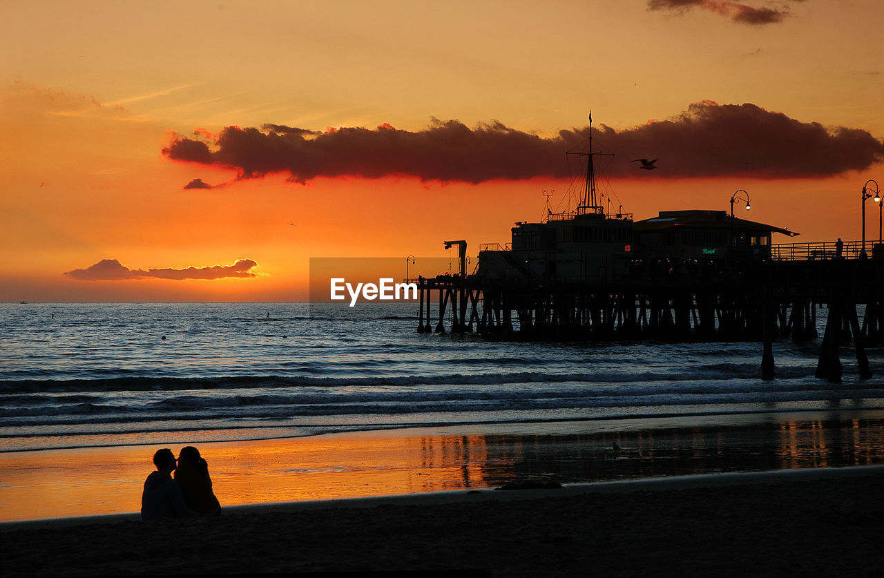 Silhouette Couple Sitting At Beach By Santa Monica Pier Against Sky During Sunset