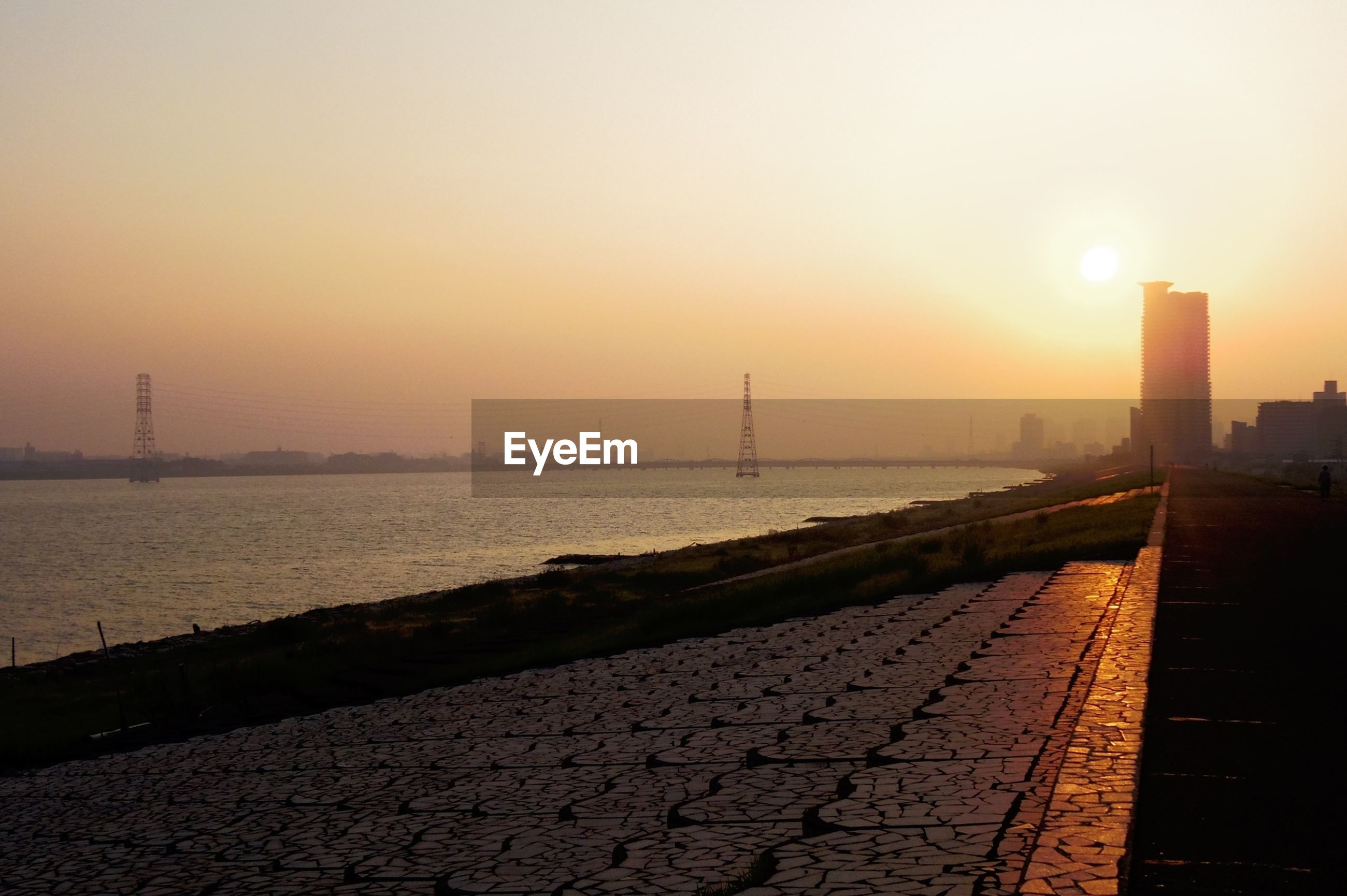 sunset, water, sea, sky, sun, tranquility, scenics, built structure, tranquil scene, silhouette, nature, orange color, beauty in nature, sunlight, the way forward, architecture, idyllic, horizon over water, outdoors, connection