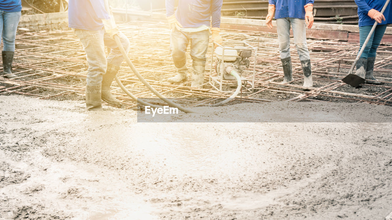 group of people, men, construction site, working, day, low section, standing, occupation, construction industry, people, group, medium group of people, development, nature, teamwork, construction worker, cooperation, real people, industry, outdoors, coworker, mud