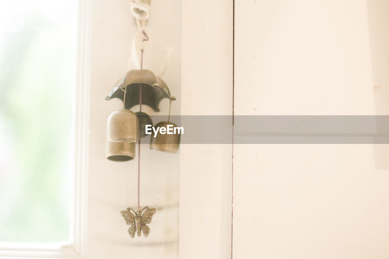 hanging, indoors, no people, home interior, wall - building feature, wood - material, metal, focus on foreground, domestic room, knob, entrance, door, window, white color, home, day, design, decoration, close-up, handle