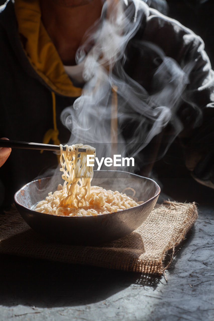 Close-up of person eating noodles