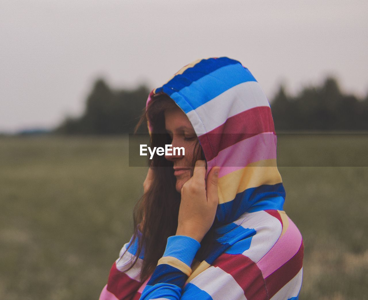 Woman with eyes closed wearing hood clothing against sky