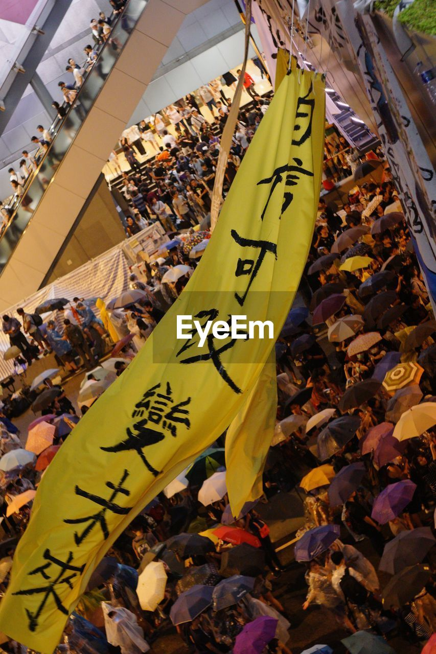 communication, yellow, text, day, high angle view, crowd, large group of people, group of people, real people, non-western script, script, close-up, protest, focus on foreground, western script, women, abundance, adult, outdoors, message, festival