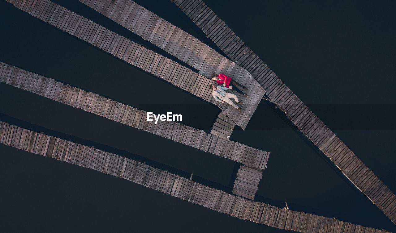 High Angle View Of Couple Lying On Pier Over Lake