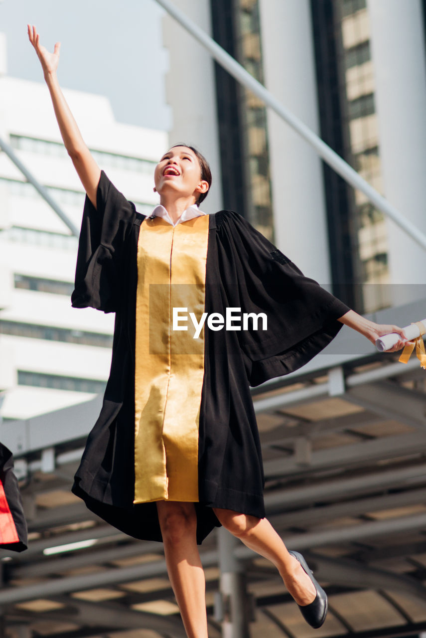 Excited Young Woman Jumping While Throwing Certificate And Mortarboard