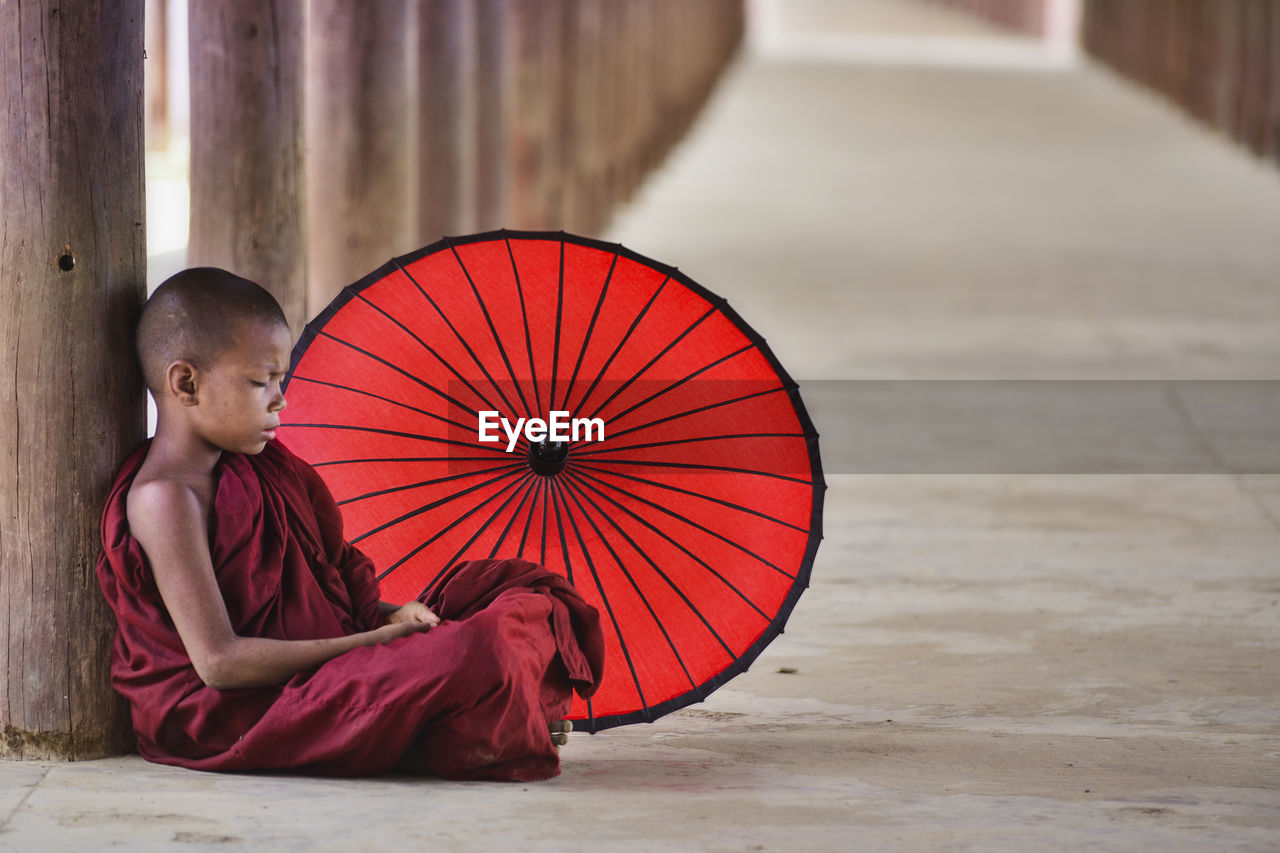 Monk with red umbrella sitting in temple