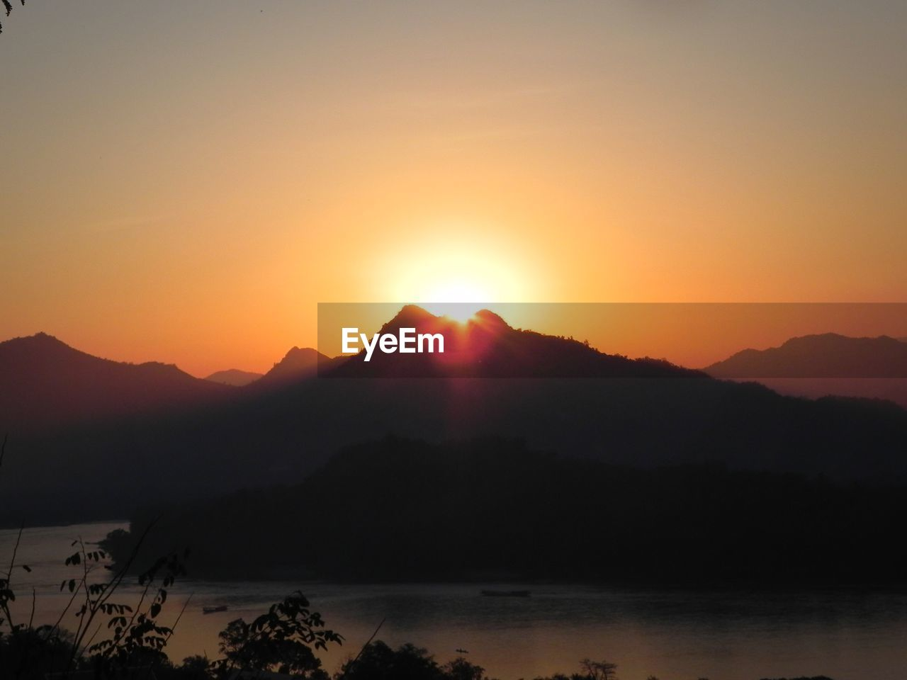 sky, sunset, beauty in nature, mountain, scenics - nature, tranquil scene, tranquility, sun, silhouette, orange color, idyllic, water, mountain range, non-urban scene, no people, nature, sunlight, environment, remote, lens flare, outdoors