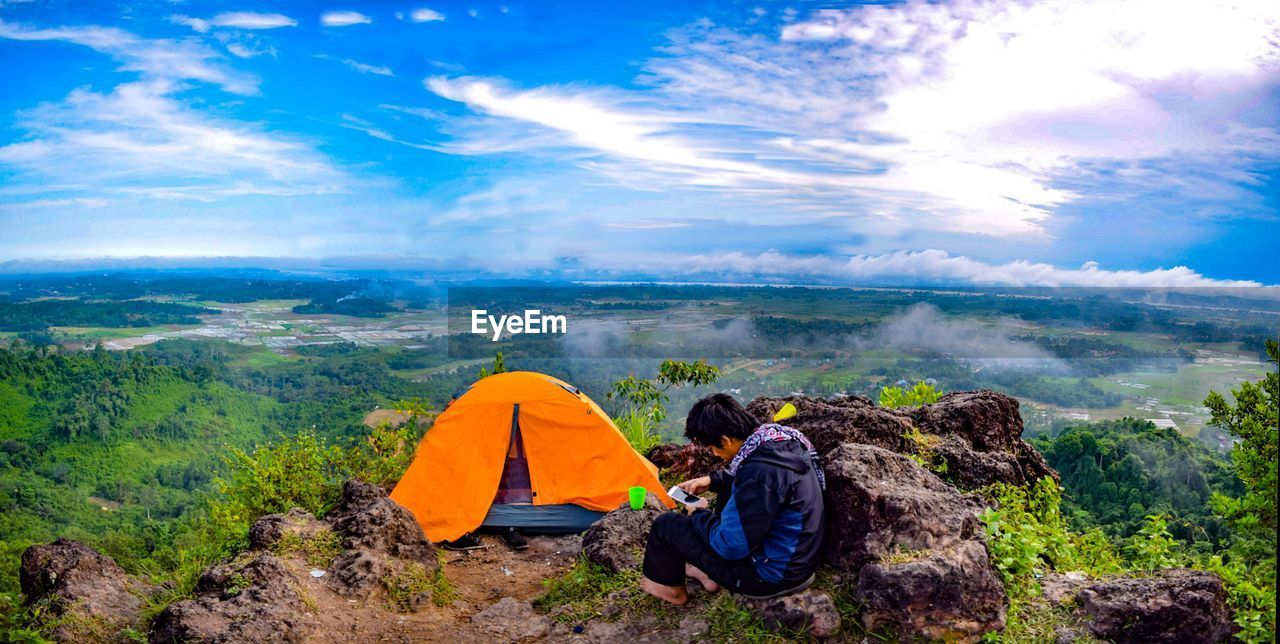 Man using mobile phone by tent on landscape against sky