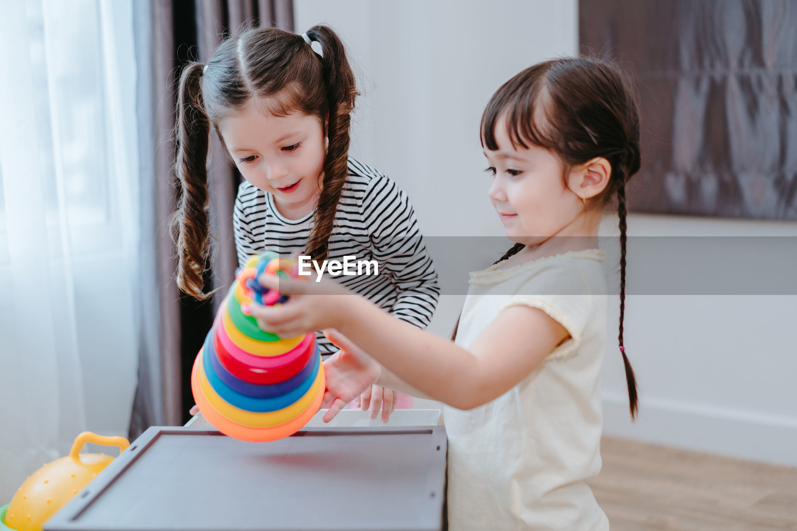 Sisters playing with multi colored toys at home
