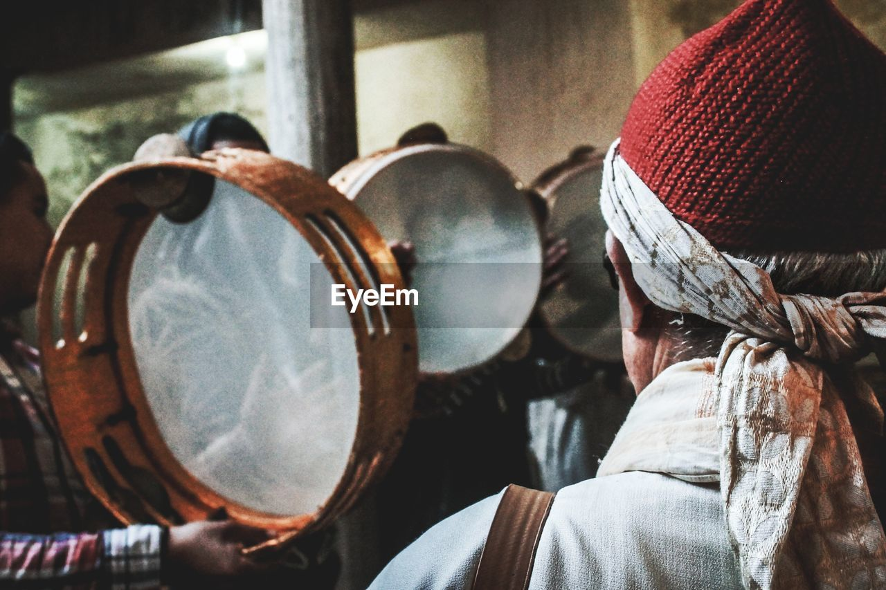 clothing, hat, real people, one person, headshot, rear view, focus on foreground, music, lifestyles, men, portrait, musical instrument, indoors, arts culture and entertainment, playing, musical equipment, close-up, unrecognizable person, leisure activity