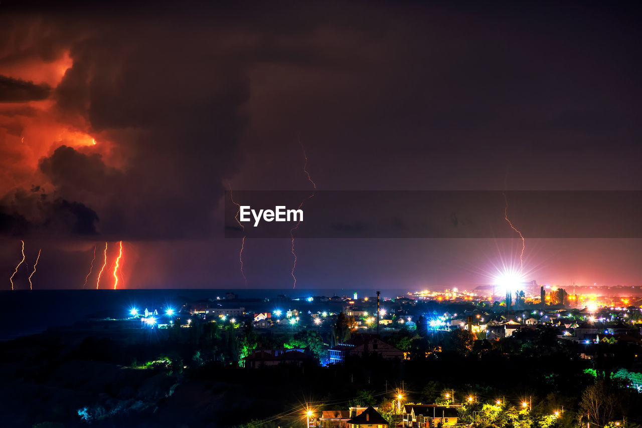 lightning, power in nature, illuminated, architecture, cloud - sky, storm, power, building exterior, night, city, thunderstorm, sky, built structure, forked lightning, no people, warning sign, communication, cityscape, sign, outdoors, light, pollution