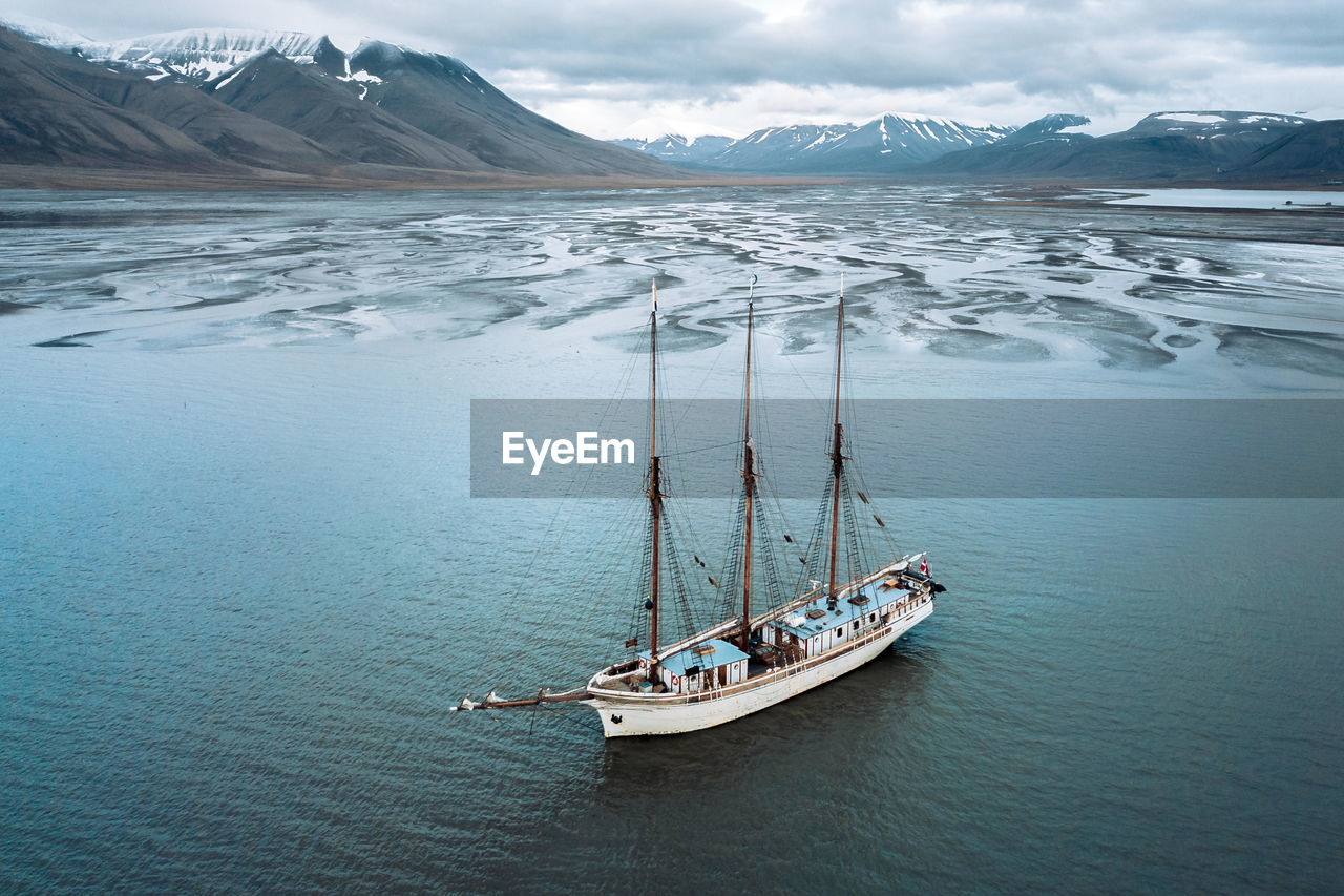 Boat Moored In Sea Against Mountains During Winter