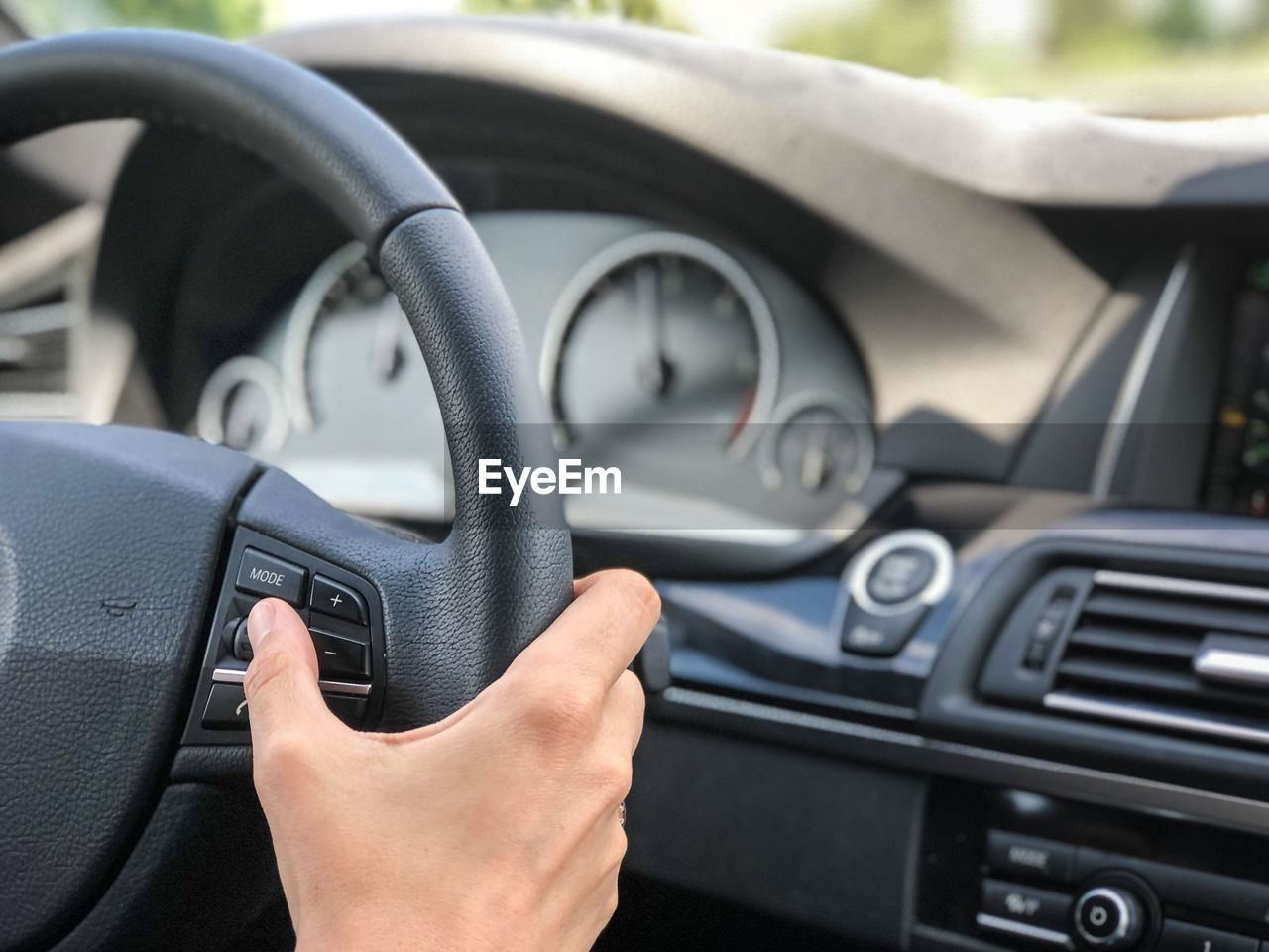 Cropped hand of woman driving car