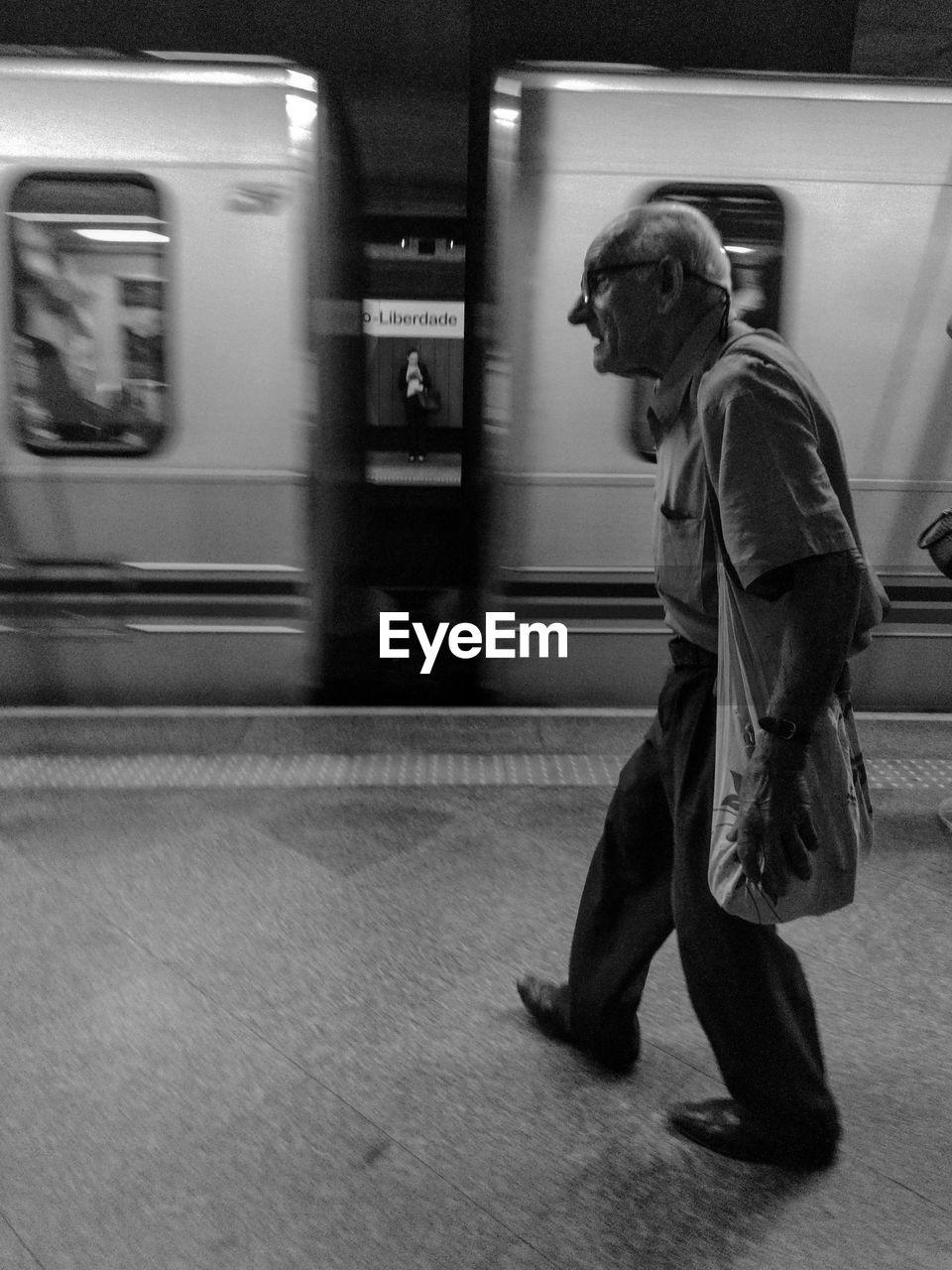 SIDE VIEW OF MAN AT RAILROAD STATION PLATFORM