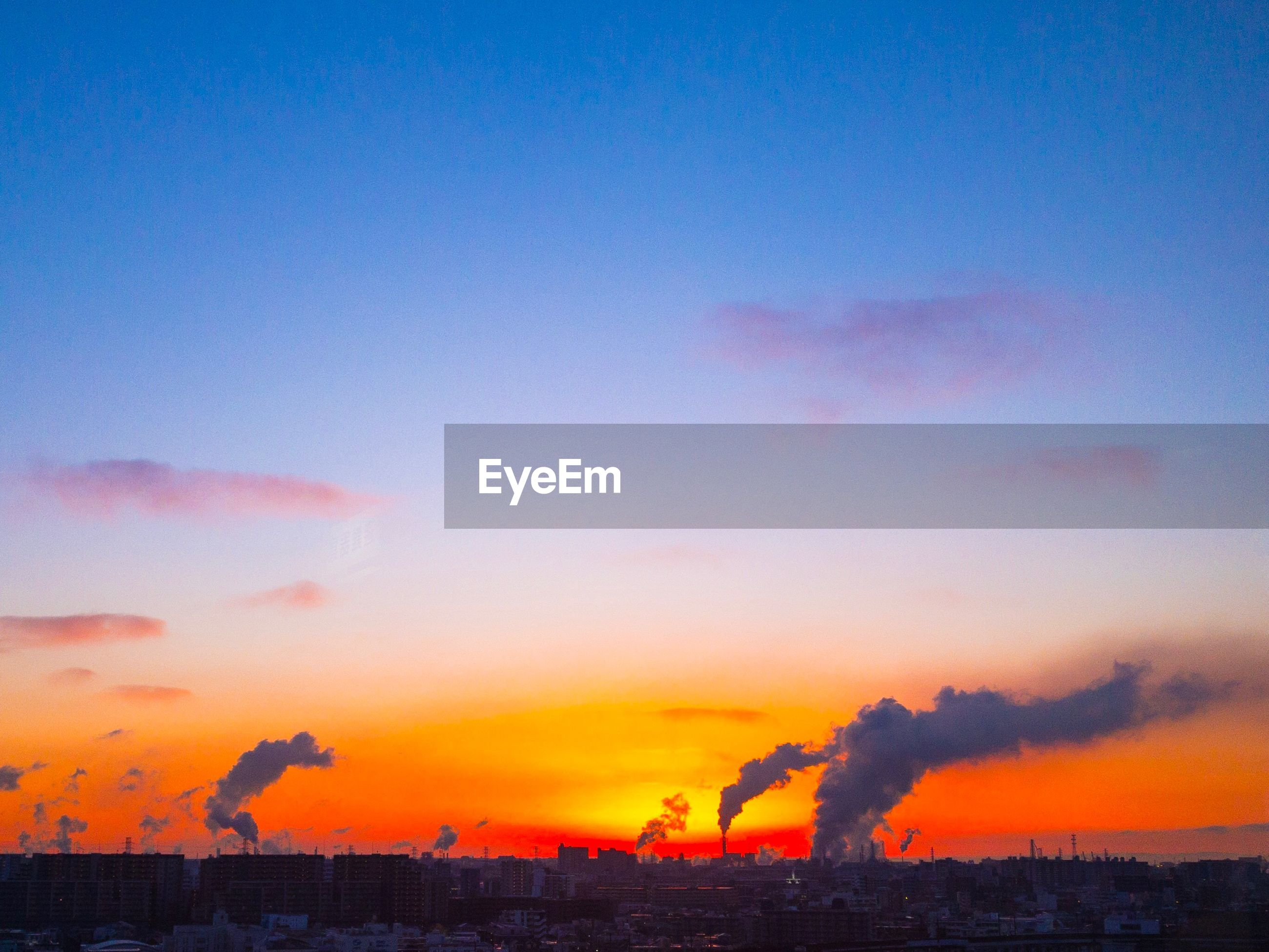 SILHOUETTE OF FACTORY AT SUNSET